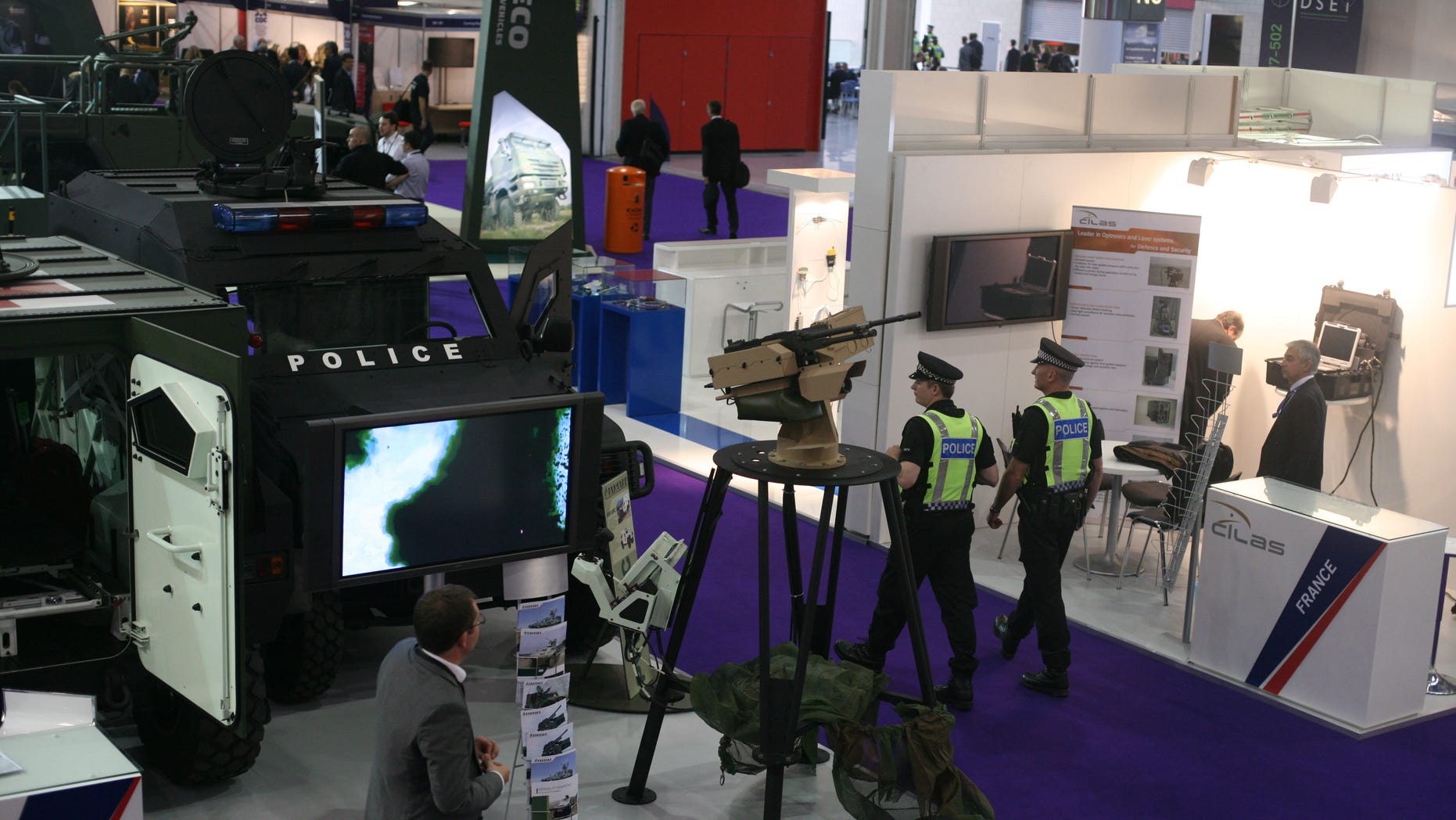 Police walk past a French Panhard armored personnel vehicle, with police markings to underscore its use beyond traditional battle fields as the Defence & Security Equipment International show gets underway in London, Tuesday Sept. 13, 2011.