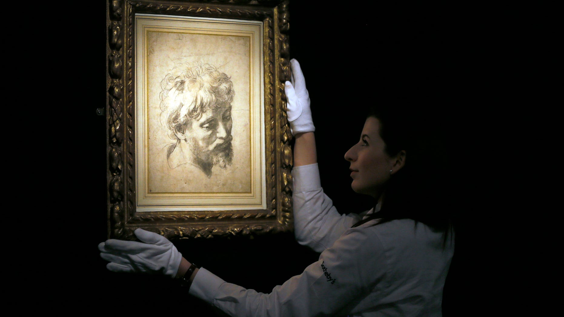 Nov. 30, 2012: A Sotheby's employee adjusts a drawing by Raffaello Sanzio, otherwise known as Raphael called 'Head of an Apostle', a Renaissance masterwork, during a press viewing in London.
