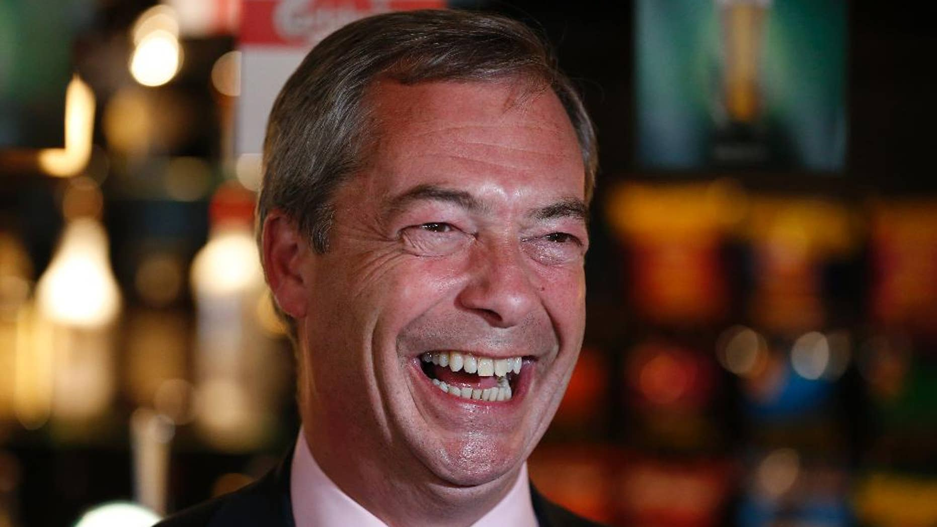 """FILE - In this Friday, May 23, 2014 file photo, Nigel Farage, leader of Britain's United Kingdom Independence Party (UKIP) smiles at a pub in South Benfleet, England. British politician Nigel Farage has defended a hotel that insisted a breast-feeding mother cover up, suggesting women might """"sit in the corner"""" while they feed their babies. Farage told LBC radio Friday Dec. 5, 2014 that women should breast-feed """"in a way that is not openly ostentatious."""" (AP Photo/Lefteris Pitarakis, File)"""