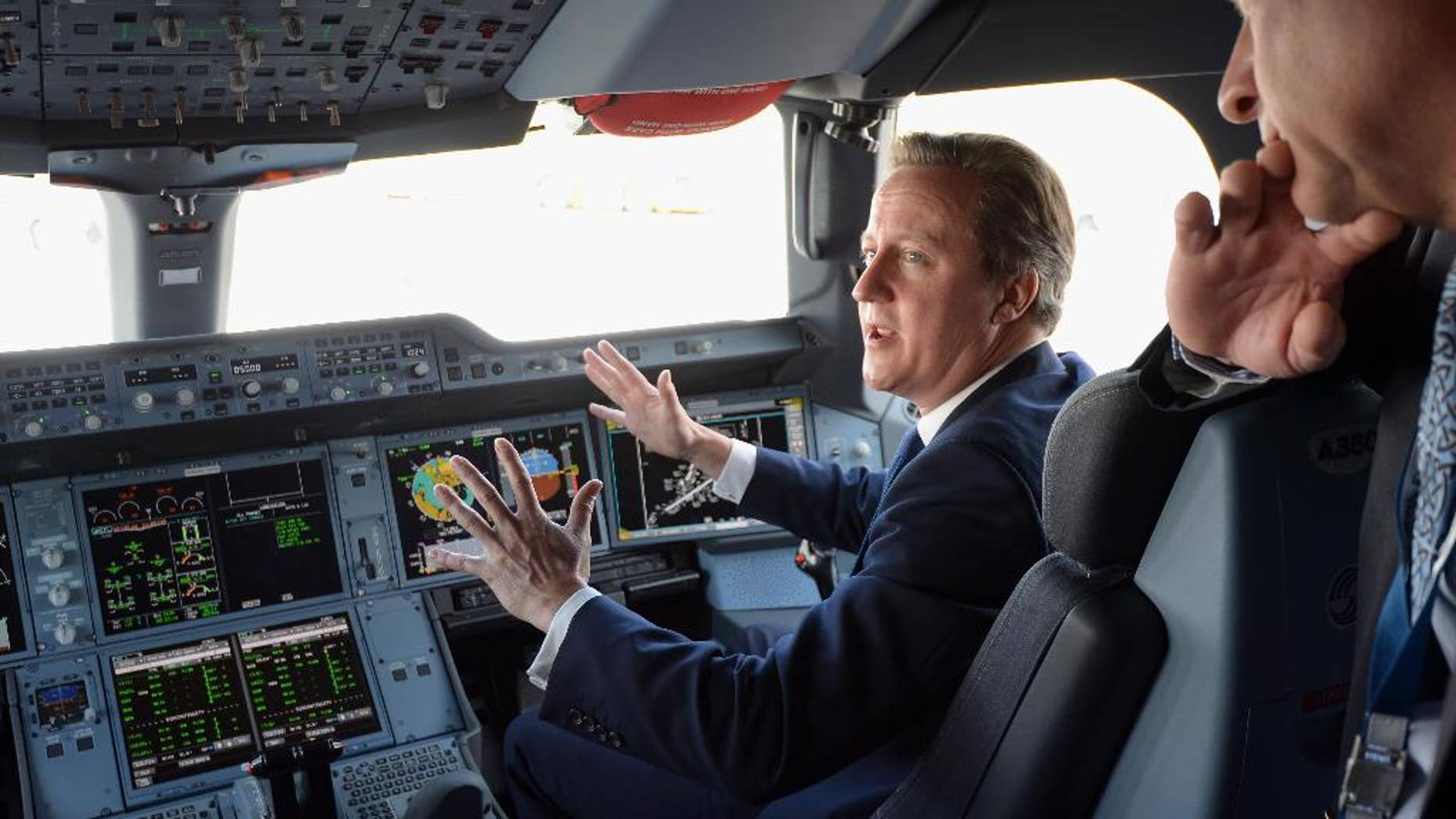 Britain's Prime Minister David Cameron, background, sits in the co-pilots seat, in the cockpit as he is shown around an Airbus A350, during a visit to the 2014 Farnborough Airshow in Hampshire, England, Monday July 14, 2014. (AP Photo/Andrew Matthews, Pool)