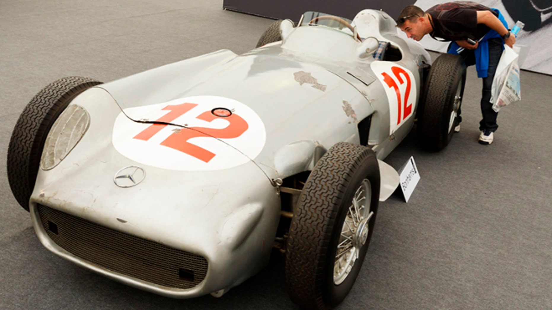 In this photo taken Thursday, July 11, 2013, a man looks inside a 1954 Mercedes-Benz W196 single-seater race car once driven by Formula One legend Juan Manuel Fangio as it is displayed by an auction house at the Festival of Speed in Goodwood, near Chichester, England. Fangio, who drove the car to victories in the 1954 German and Swiss Grand Prix race, sold for 19.6 million pounds ($29.6 million) at auction on Friday. (AP Photo/PA, Chris Ison) UNITED KINGDOM OUT, NO SALES, NO ARCHIVE