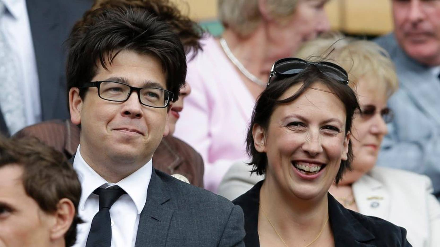 """FILE - This is a Saturday, July 7, 2012  file photo of British comedian Michael McIntyre, left, and comedian Miranda Hart, as they watch Serena Williams of the United States face Agnieszka Radwanska of Poland in the women's final match at the All England Lawn Tennis Championships at Wimbledon, England.  An image of the top of Micheal McIntyre's  head has Britons debating the decline of privacy in an age of surveillance. On Wednesday July 15, 2015 the National Police Air Service, which operates camera-equipped helicopters, tweeted an image of a man with a mop of dark hair, asking if people could recognize """"a certain energetic funny man."""" (AP Photo/Kirsty Wigglesworth, File)"""
