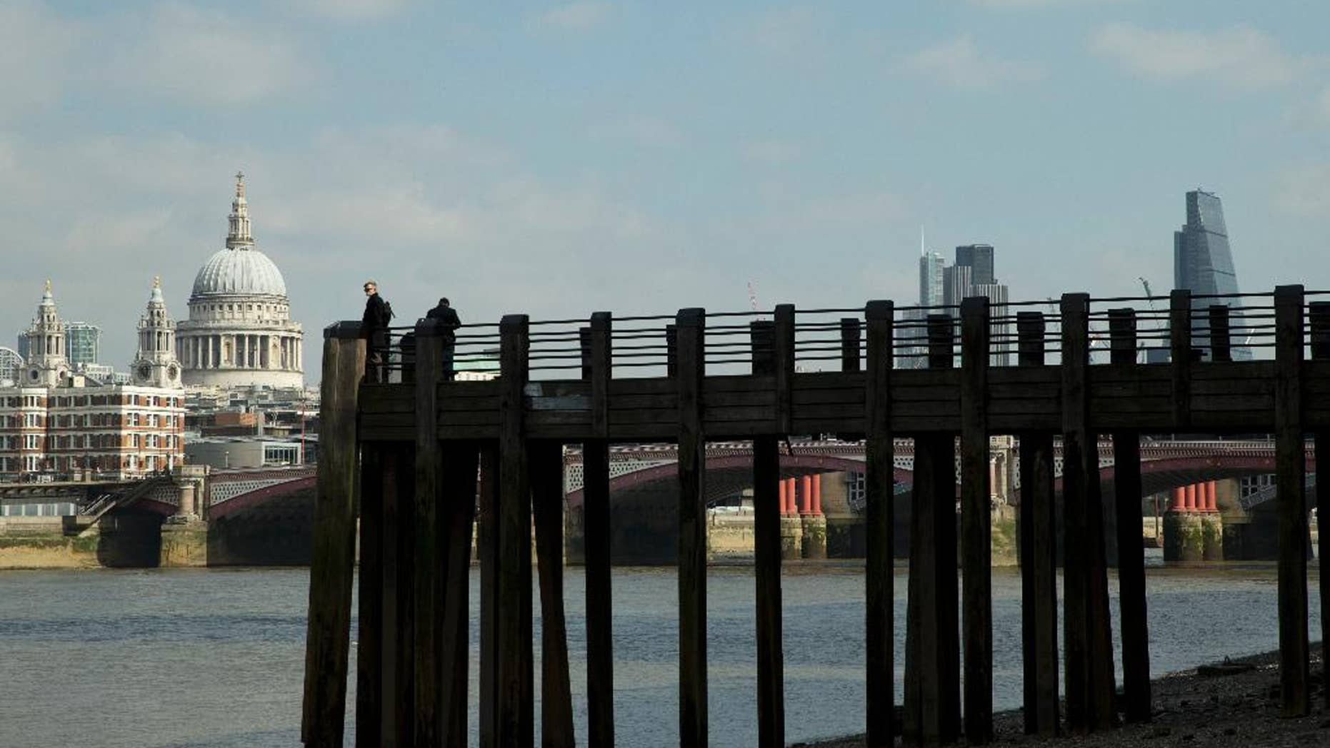 Tourists take photos of the River Thames, with St Paul's Cathedral, left, at low tide on the south bank in London, Monday, March 23, 2015. (AP Photo/Alastair Grant)