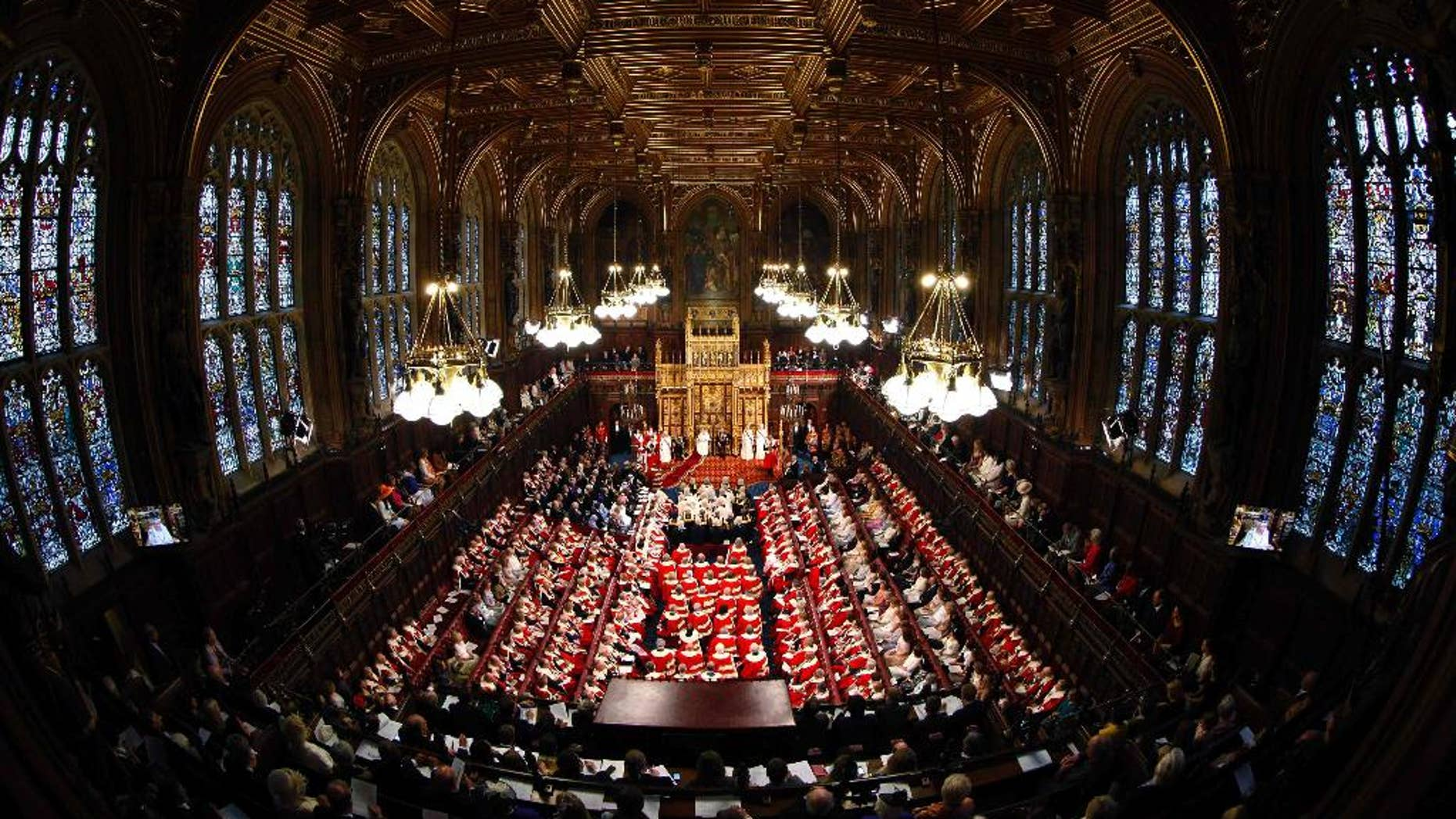 FILE - This is a Wednesday June 4, 2014  file photo of Britain's Queen Elizabeth, rear centre, as she delivers her speech in the House of Lords, during the State Opening of Parliament at the Palace of Westminster in London . An annual speech, read by the monarch at the ceremonial State Opening of Parliament, the Queen's Speech is written by the government and outlines its legislative program. Winning the vote that follows is crucial to the survival of any government. This year's Queen's Speech will be May 27, when either Conservative leader David Cameron or Labour's Ed Miliband will unveil his government's plans. (Suzanne Plunkett/Pool Photo via AP, File)