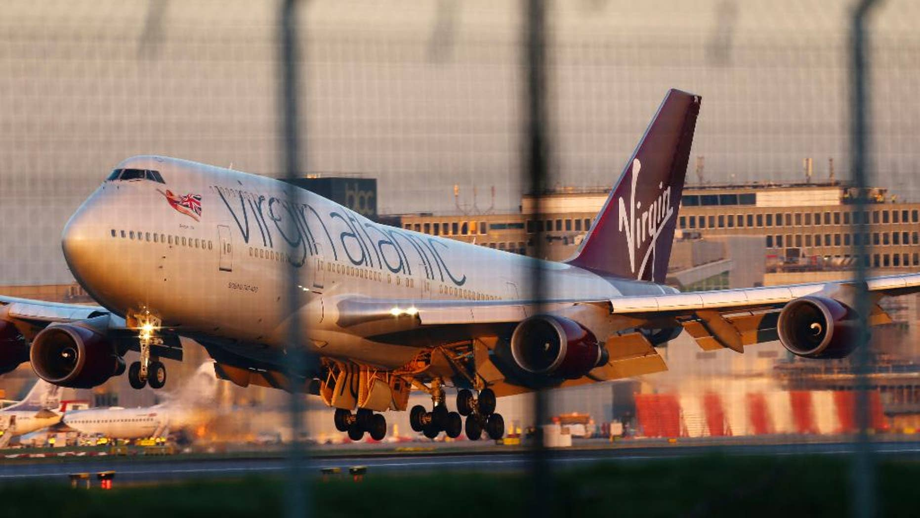 """A Virgin Atlantic Boeing passenger jet performs an emergency landing at Gatwick Airport after developing a landing gear fault, London, Monday, Dec. 29 2014. The airline says the plane undertook """"a non-standard landing procedure"""" because of """"a technical issue with one of the landing gears."""" (AP Photo/PA, Gareth Fuller) UNITED KINGDOM OUT, NO SALES, NO ARCHIVE"""