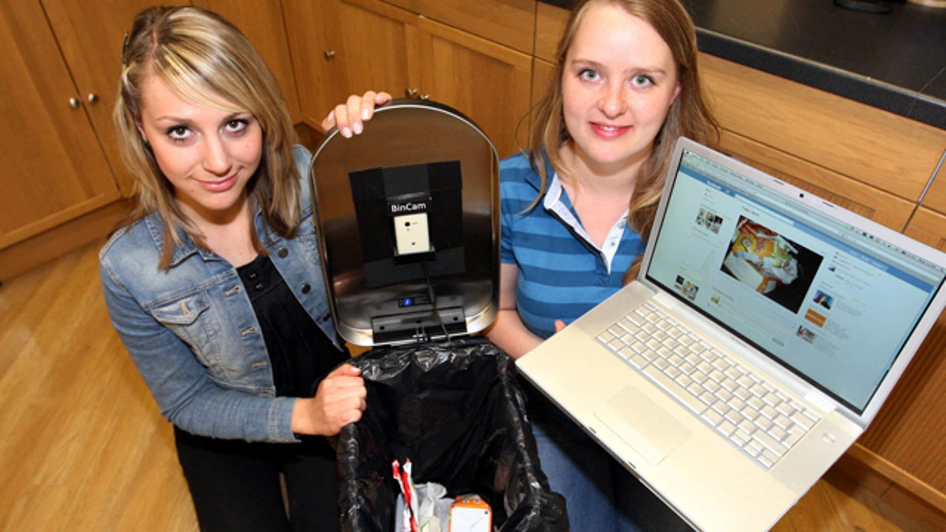 June 8, 2011: Newcastle University students Julia Miebach, left, and Anja Thieme, right, with the Bincam and a laptop showing its Facebook page. Five households have signed up for a program announced Wednesday that puts photographs of every item placed in a garbage can on Facebook, to raise consciousness about recycling efforts.