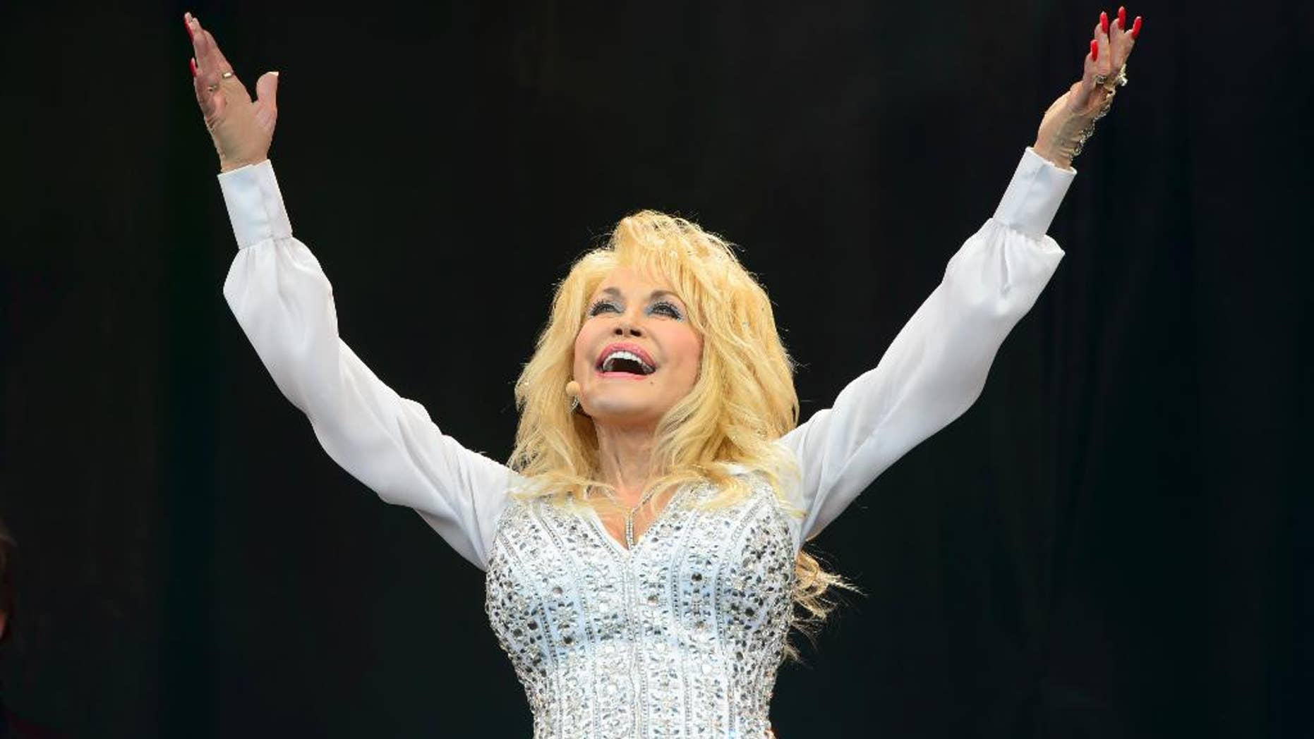 """FILE - In this Sunday, June 29, 2014 file photo, U.S singer Dolly Parton performs at Glastonbury music festival, England. Dolly Parton wants to take an unlikely fan home with her. Dolly"""" the dog was found abandoned at Britain's Glastonbury music festival in one of the thousands of tents which spring up every year at the countryside festival, famous for rain and mud as much as its star performers.  After Parton wowed more than 150,000 people she heard about the dog with the fluffy white coat and offered to adopt it. """"I will take the dog home to America if nobody claims her,"""" she said in a statement Sunday, July 6, 2014.  (Photo by Jonathan Short/Invision/AP, File)"""