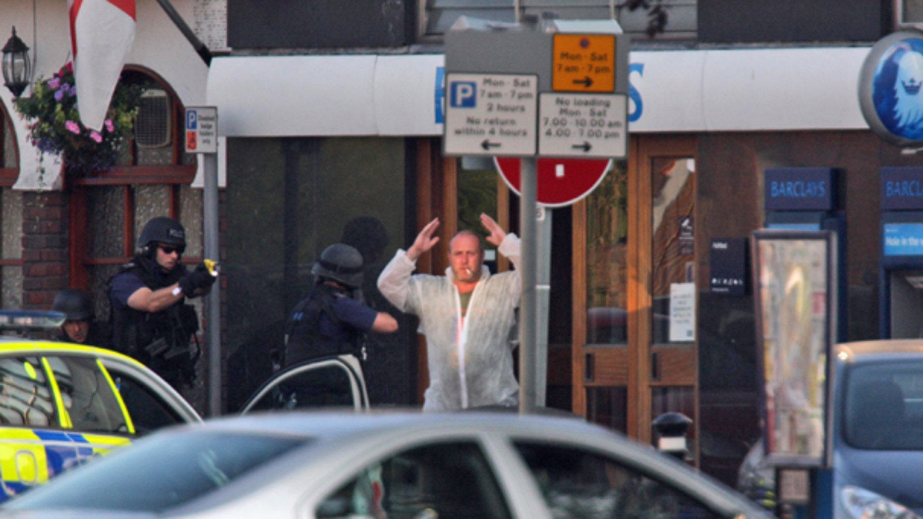 June 28: Armed police cover a man as he leaves a Barclays bank with his hands up in Ashford, England.  Armed officers deployed to the scene of a possible hostage situation at a bank near London's Heathrow Airport. (AP)