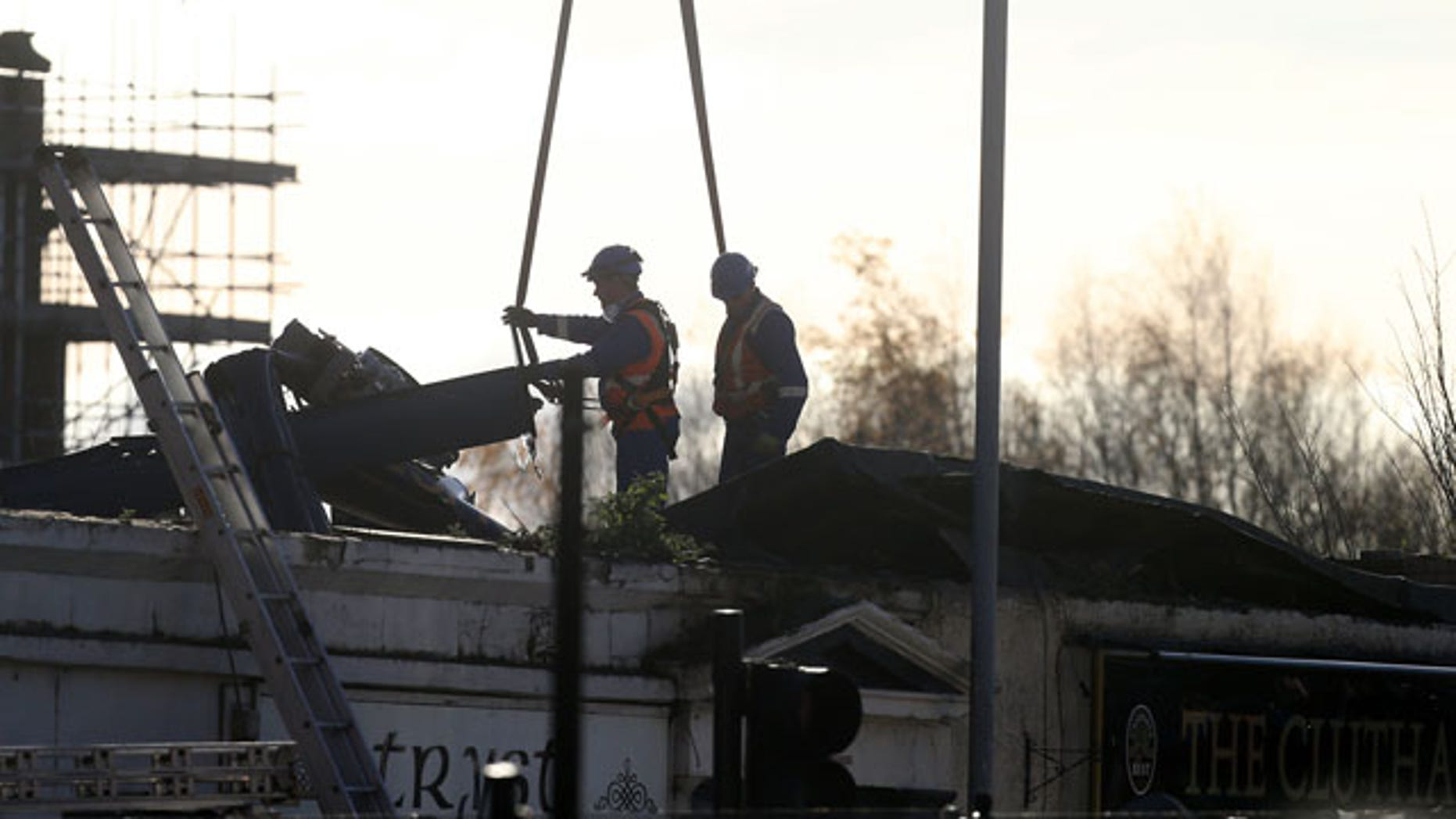 December 1, 2013: Scottish Fire and Rescue services look on at a section of the helicopter being lifted from the scene following the helicopter crash at the Clutha Bar in Glasgow, Scotland. (AP Photo)