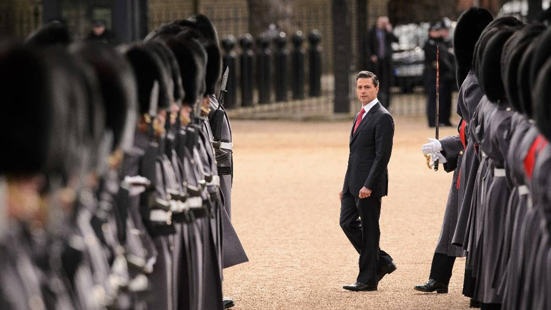 Mexican President Enrique Pena Nieto, centre, inspects a Guard of Honour during a ceremonial welcome in central London on Tuesday  March 3, 2015. The President and his wife are on a 3 day state visit to Britain. (AP Photo/Loen Neal, Pool)