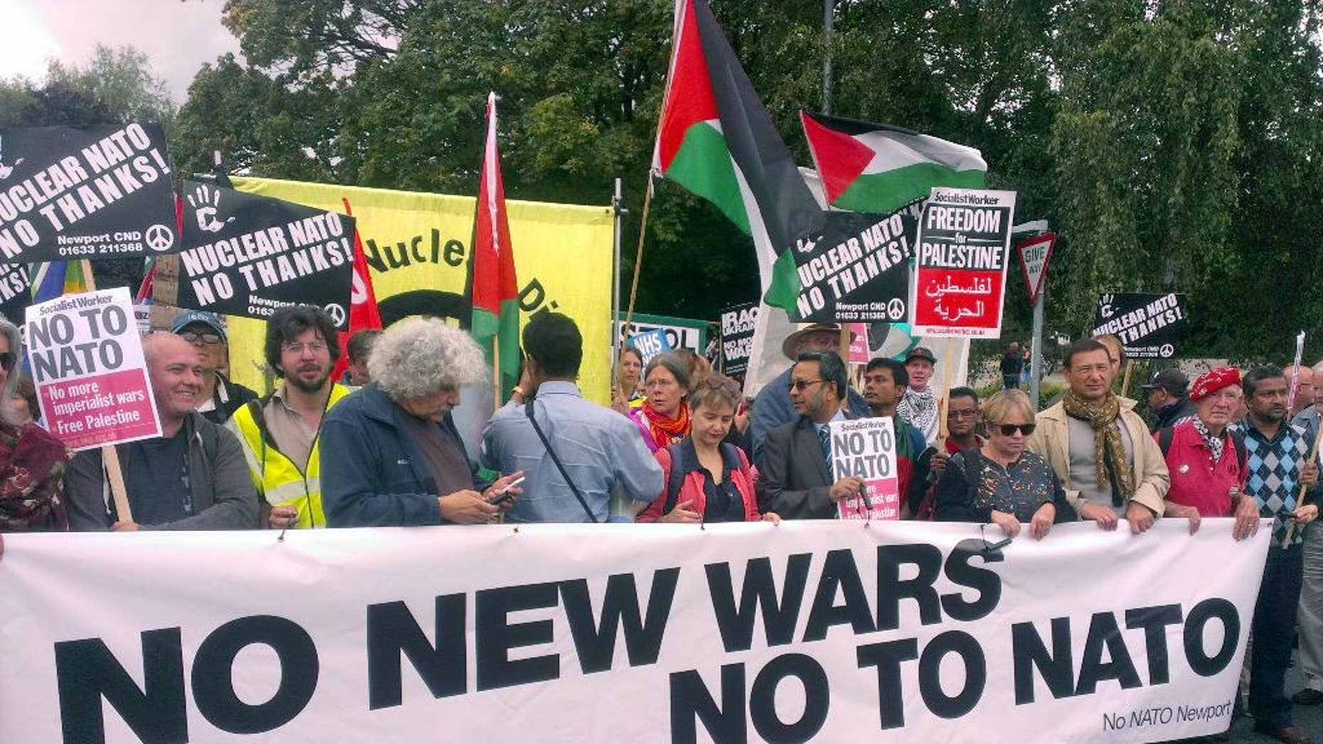 """Supporters take part in the 'No to NATO' protest march in Newport, south Wales, Saturday, Aug. 30, 2014. Around 1,000 protesters have marched through the streets of Newport ahead of next week's NATO summit. More than 150 heads of state and ministers will attend the two-day event at Newport's Celtic Manor Resort. The event will be """"uncharted territory"""" for police - while Wales' First Minister Carwyn Jones has said it will be """"momentous"""" in his country's history. However, its presence in the principality - and the UK - has been met with strong opposition from a number of anti-war groups as well as left-wing organizations. A large crowd gathered outside Newport Crown Court at around midday before going on a march through the Welsh city. As well as strong Welsh contingent, protesters came from as far as Washington, Belgium, France and Ireland. (AP Photo/Benjamin Wright, PA Wire)     UNITED KINGDOM OUT    -   NO SALES    -    NO ARCHIVES"""