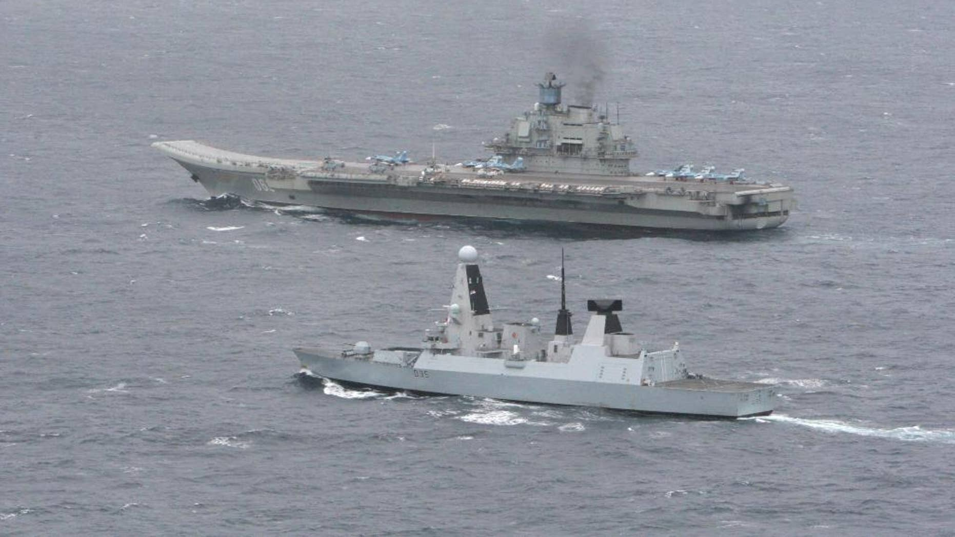 """An undated aerial photo made available by Britain's Ministry of Defence, Thursday, May 8, 2014 showing HMS Dragon, foreground, with the Russian aircraft carrier 'Admiral Kuznetsov' in the English Channel. The Royal Navy warship met and tracked a Russian task force group as it entered the English Channel in an operation that the Ministry of Defense repeatedly stressed was a routine matter. HMS Dragon, a Type 45 destroyer, monitored the movement of the seven-strong Russian group led by the aircraft carrier Admiral Kuznetsov. The navy says that once the ships spotted each other they """"sailed close by as a standard 'meet and greet.' '' (AP Photo/Ministry of Defence)"""