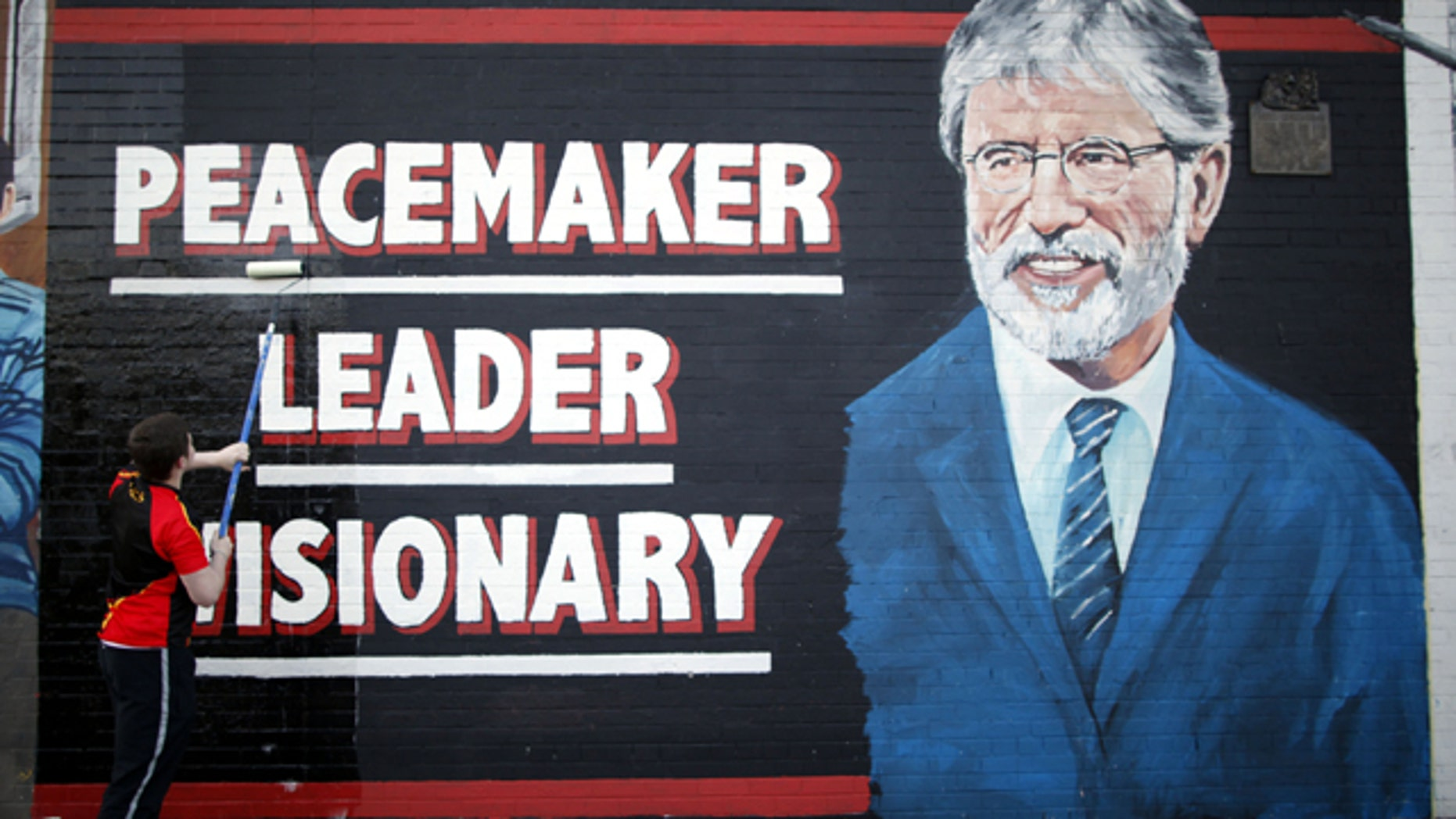 May 2, 2014: A man adds the finishing touch to a newly painted mural of Sinn Fein leader Gerry Adams on the Falls Road, West Belfast, Northern Ireland. (AP Photo/Peter Morrison)