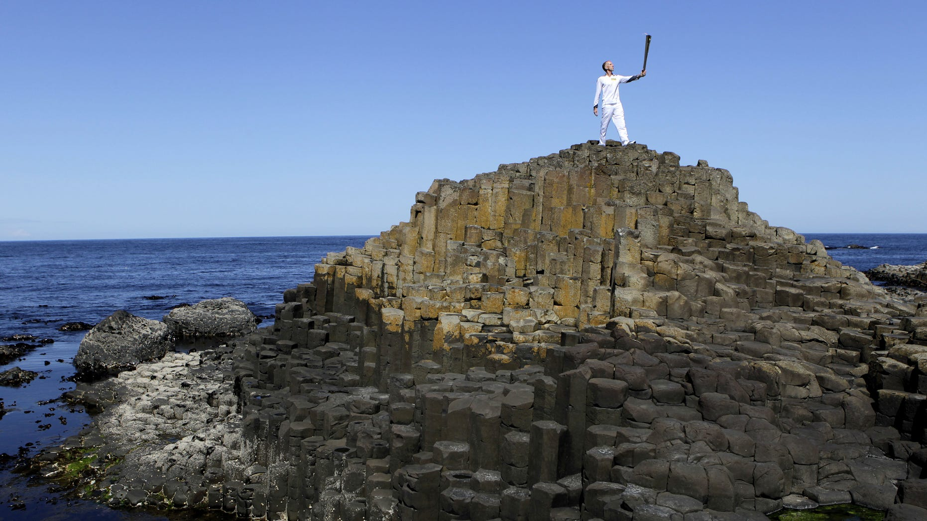 Peter Jack holds the Olympic torch aloft at the Giant's Causeway in county Antrim, Northern Ireland, Monday, June 4, 2012.   The Olympic Torch is continuing its relay journey around the country, and is scheduled to arrive at the opening ceremony of the London 2012 Olympic Games. (AP Photo/Peter Morrison)