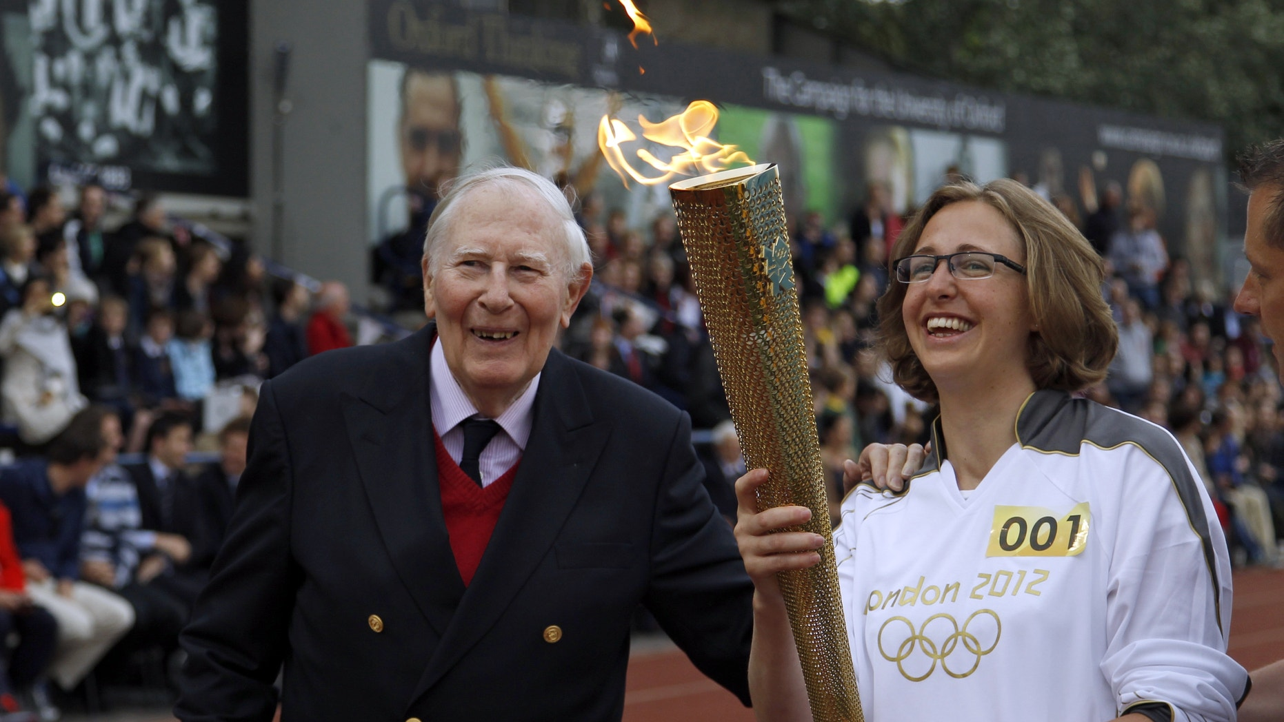 July 10, 2012: The Olympic Flame is passed between Sir Roger Bannister and Oxford doctoral student Nicola Byrom on the running track at Iffley Road Stadium in Oxford, England.