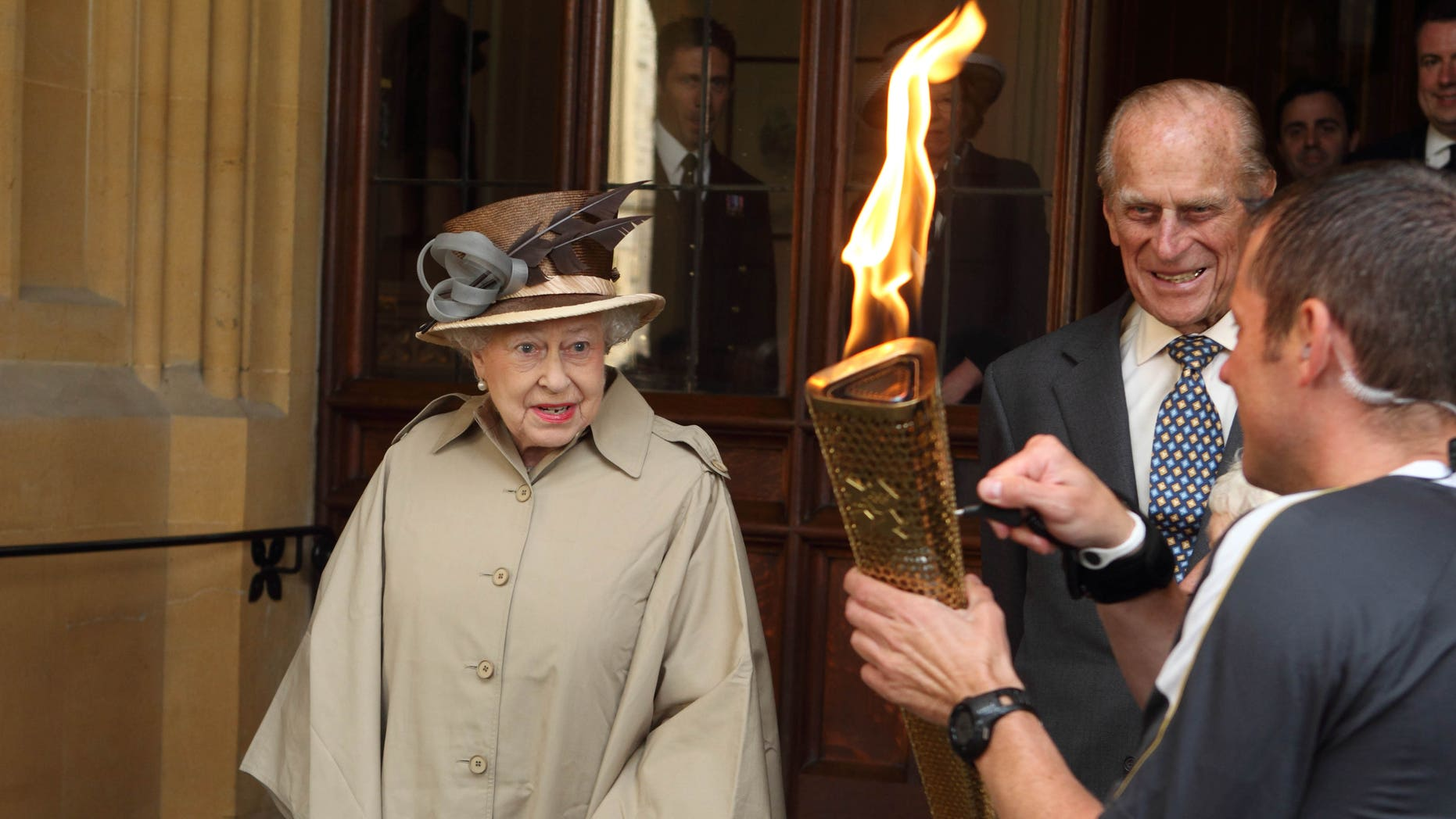 July 10, 2012: Britain's Queen Elizabeth II and Prince Philip look at the Olympic Flame at Windsor Castle, Windsor, England.