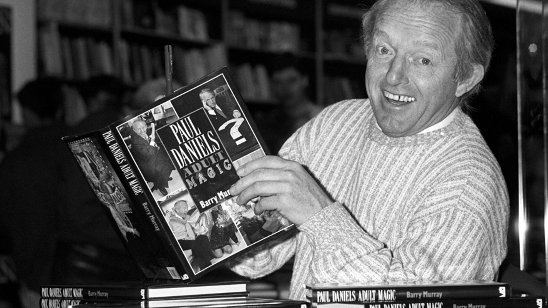 This is a Dec. 2, 1989 file photo of British magician Paul Daniels as he holds with a copy of his book 'Adult Magic' at Whiteleys book shop in London.