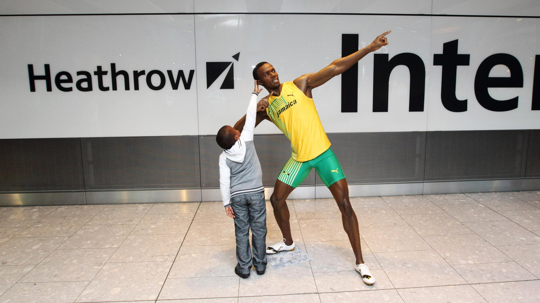 July 12, 2012: A child reaches up to touch the wax figure of Usain Bolt, as passengers arrive at London's Heathrow Airport Terminal 5, are greeted by the wax figure.