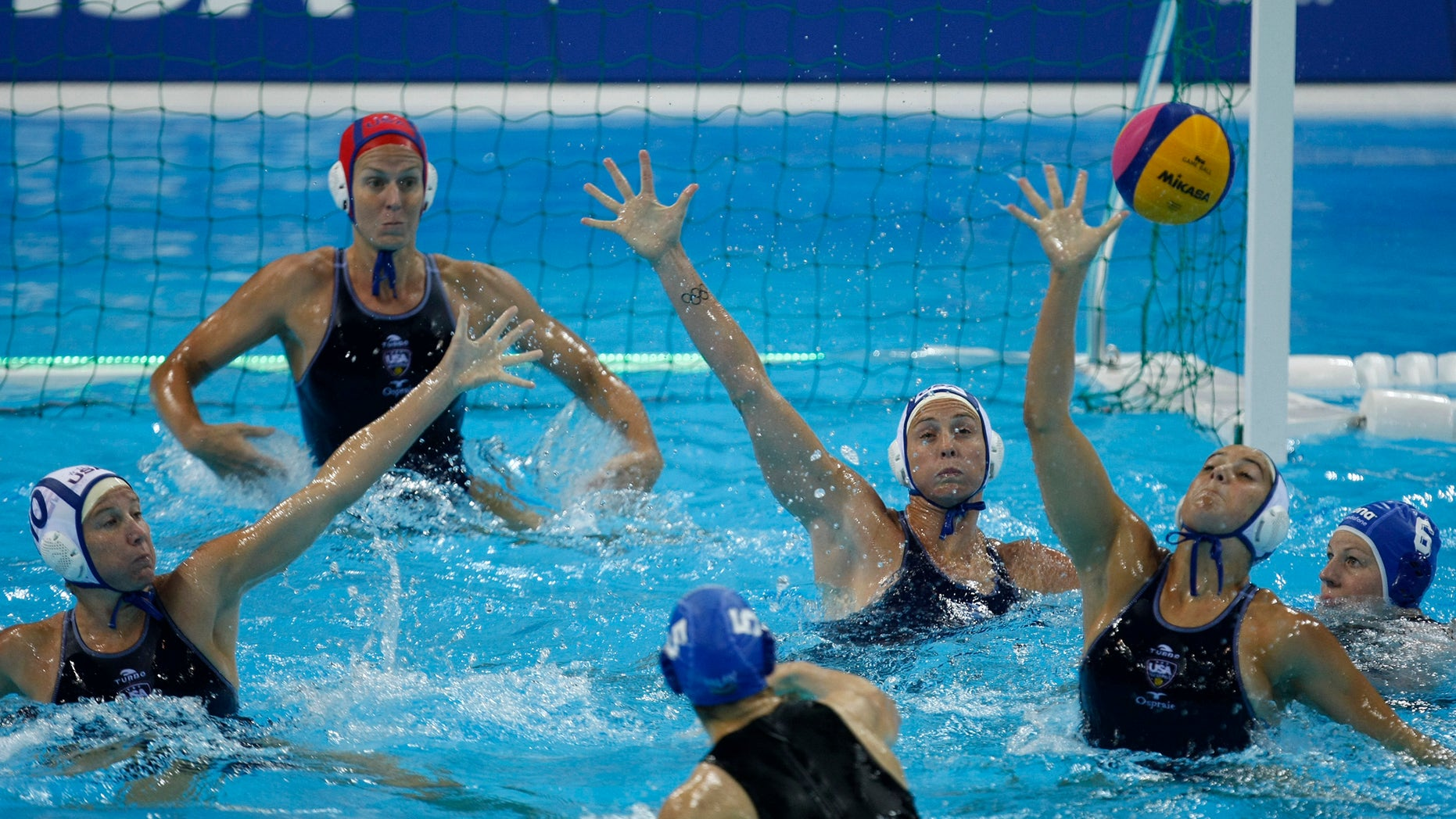 May 3, 2012: Gabriella Szucs, of Hungary, No 5, at bottom, shoots and scores a goal against the US during their international  Women's Water Polo event, preliminary round, at the London 2012 Olympic water polo pool in London.