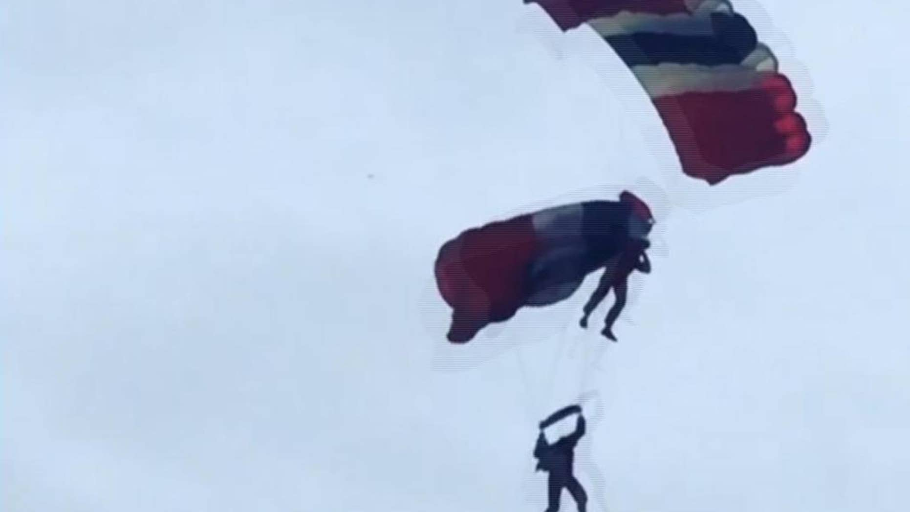 "This image taken from video provided by Ricky Parnaby shows a member of the British military stunt team, The Red Devils, receiving assistance from a teammate after his parachute failed to open properly whilst performing Friday, June 19, 2015 at the Whitehaven Airshow in northwestern England. A message posted on the show's Facebook page assured spectators that both were fine after ""one team member caught his teammate and brought him into Queens Dock."" The parachutists landed in water and were plucked to safety. (Ricky Parnaby via AP)  MANDATORY CREDIT"