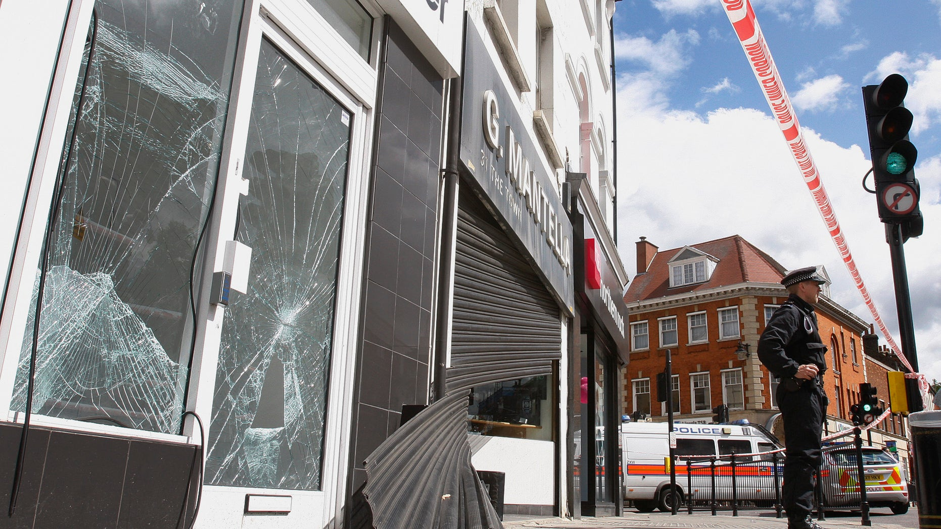 "August 8: Smashed glass doors and windows and wrecked shutters on the shop front of a betting shop and a jewelry shop in Enfield, north London. British police on Monday promised a ""momentous operation"" to arrest rioters after a weekend of vandalism and looting that erupted in a disadvantaged London neighborhood just miles (kilometers) from the site of next year's Olympic Games."