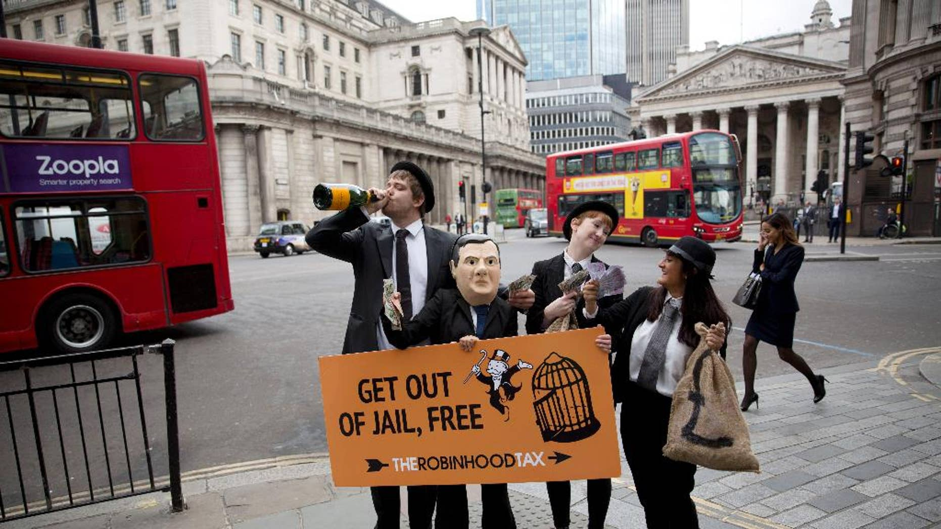 Campaigners from the Robin Hood Tax organization dressed as bankers, including one wearing a mask representing British Chancellor of the Exchequer George Osborne, hold placards as they pose for the media outside Mansion House, backdropped by the Bank of England at left, in London, Wednesday, June 10, 2015. The group say their idea for a Robin Hood Tax is a tiny tax on the financial sector that could generate billions of pounds annually to fight poverty and climate change. The stunt was held by the group to coincide with Osborne's annual economic speech due to be held at Mansion House on Wednesday evening.  (AP Photo/Matt Dunham)