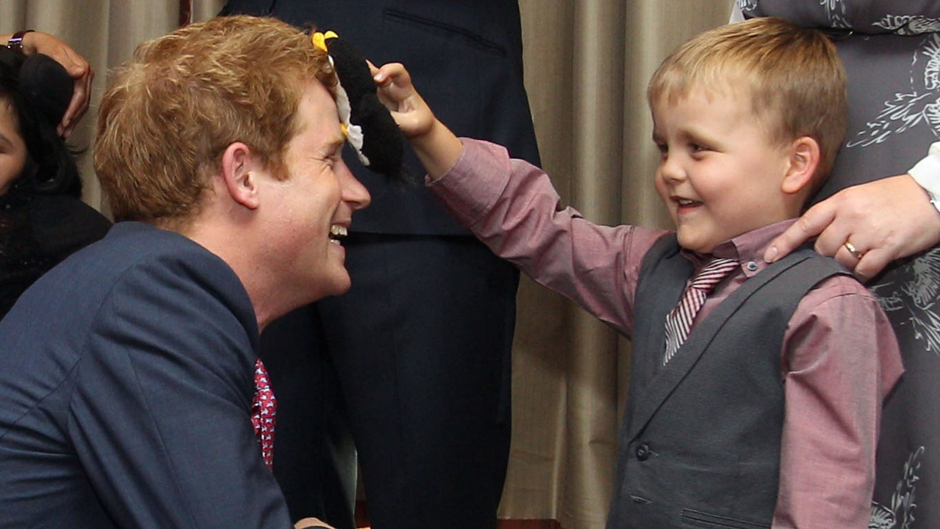 Sept. 3, 2012: Britain's Prince Harry talks to Alex Logan, right,  who puts a toy penguin against his head, as he attends the WellChild awards ceremony InterContinental Park Lane Hotel, London.