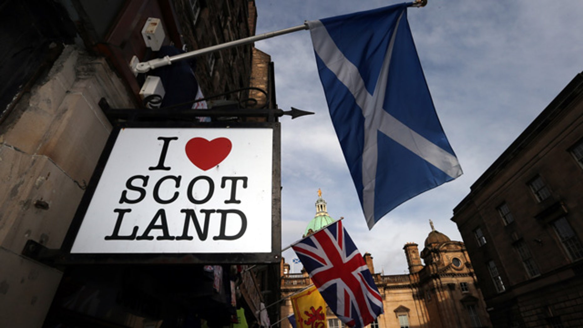 FILE - In this Thursday, Feb. 13, 2014, file photo a Scottish flag and a Union flag fly outside a Scottish memorabilia shop in Edinburgh, Scotland. (AP Photo/Scott Heppell, File)
