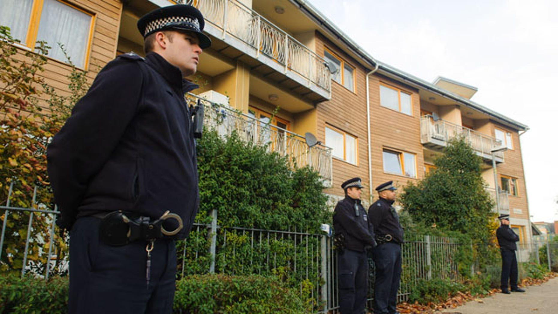 November 23, 2013: Police officers stand outside flats as police conduct house-to-house inquires in the area where three women were rescued in south London. UK police said Saturday that a collective living situation based on shared political beliefs is at the root of a major slavery case that led to the arrest of two suspects this week.