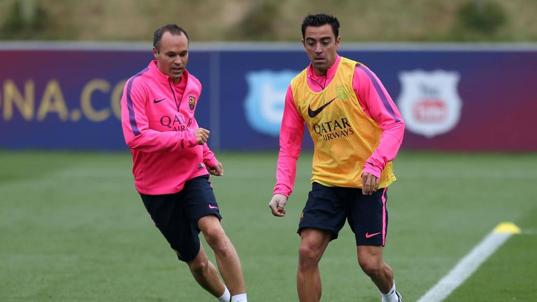 Barcelona's Xavi, right,  and Andres Iniesta, run, during a pre-season training session, at St George's Park, Burton-Upon-Trent,  England,  Friday Aug.  1, 2014. (AP Photo/PA, Simon Cooper) UNITED KINGDOM OUT