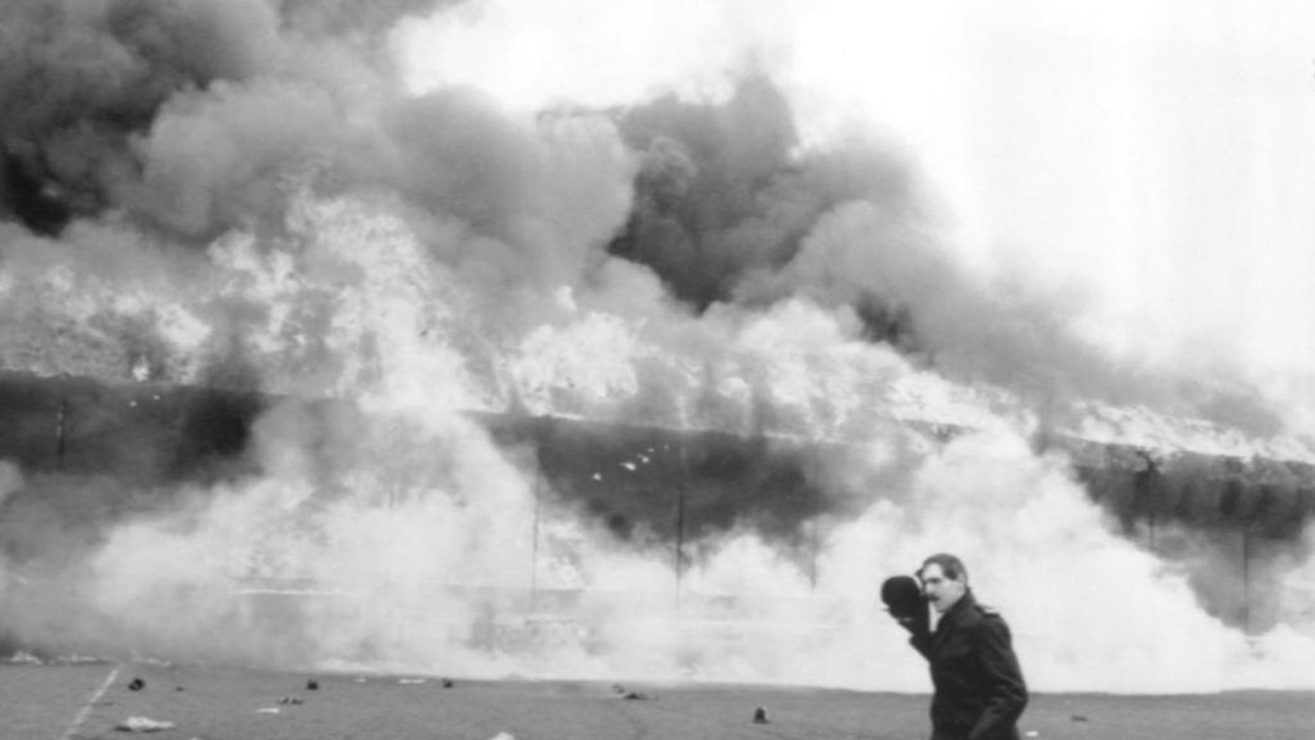 FILE - In this May 11, 1985 file photo, a police officer runs past the blazing main stand at Bradford City's Valley Parade football ground in Bradford, England. It's approaching 30 years since Valley Parade, Bradford's home ground, became an inferno. Fifty-six spectators died and 265 were injured when a fire broke out and engulfed a wooden main stand holding about 3,500 fans during the team's final match of the season against Lincoln. (PA via AP, File) UNITED KINGDOM OUT, NO SALES, NO ARCHIVE