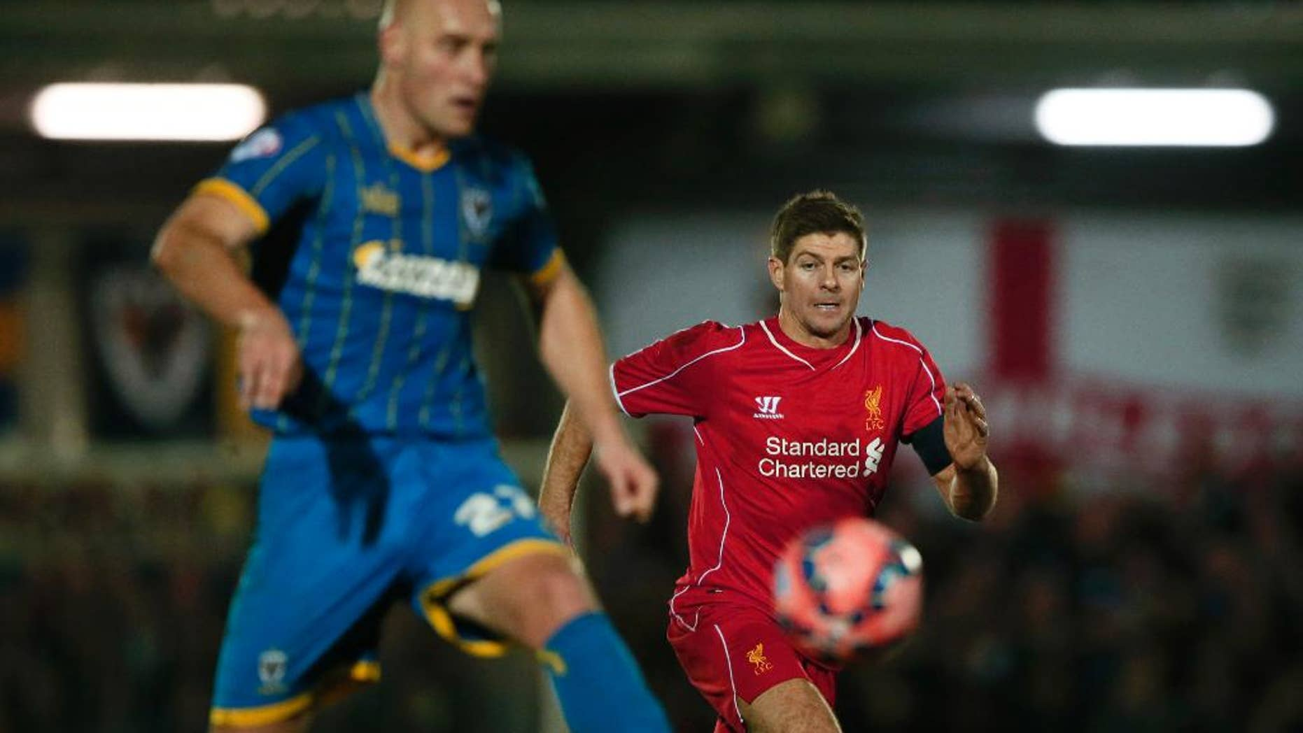 Liverpool's Steven Gerrard, right watches as =AFC Wimbledon's Adam Barratt passes back to his goalkeeper during their English FA Cup third round soccer match between AFC Wimbledon and Liverpool in Kingston, London, Monday, Jan.  5, 2015 . (AP Photo/Alastair Grant)