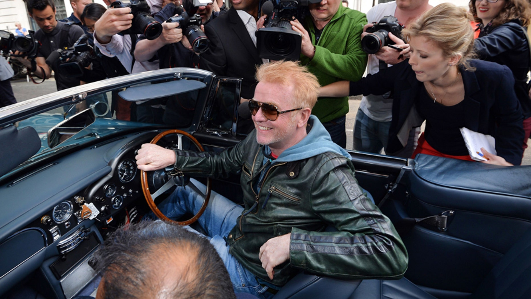 """Media flock around radio and TV personality, Chris Evans as he leaves the BBC Radio studios in London, Wednesday June 17, 2015, driving his vintage Aston Martin car, after he was announced as the new Top Gear presenter.  The BBC TV company says its top automotive TV show """"Top Gear"""" will return to the airwaves with Chris Evans as the new host, replacing scandal-tainted Jeremy Clarkson, who was sacked for punching one of the show's producers. (John Stillwell  / PA via AP) UNITED KINGDOM OUT - NO SALES - NO ARCHIVES"""