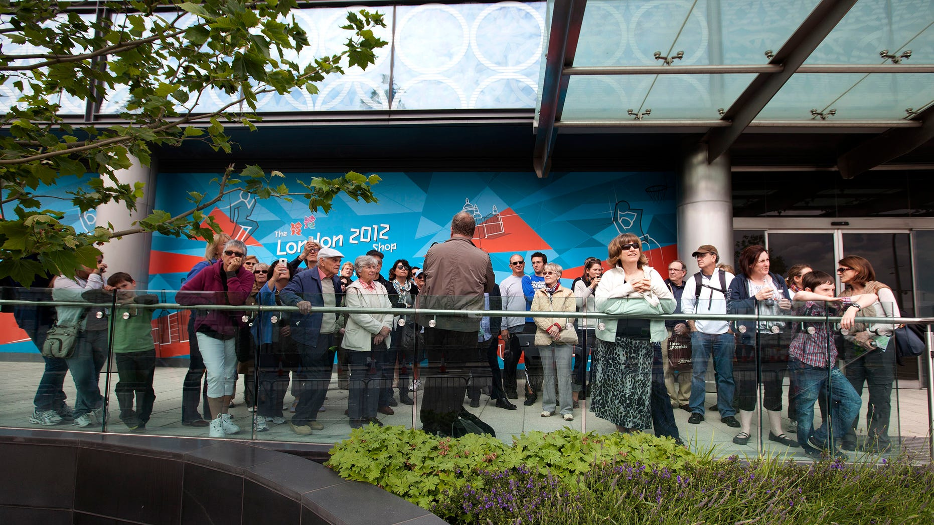 June 13, 2012: In this photo tour guide Andy Rashleigh, back to camera, talks to his tour group  near the London 2012 Olympic Park.