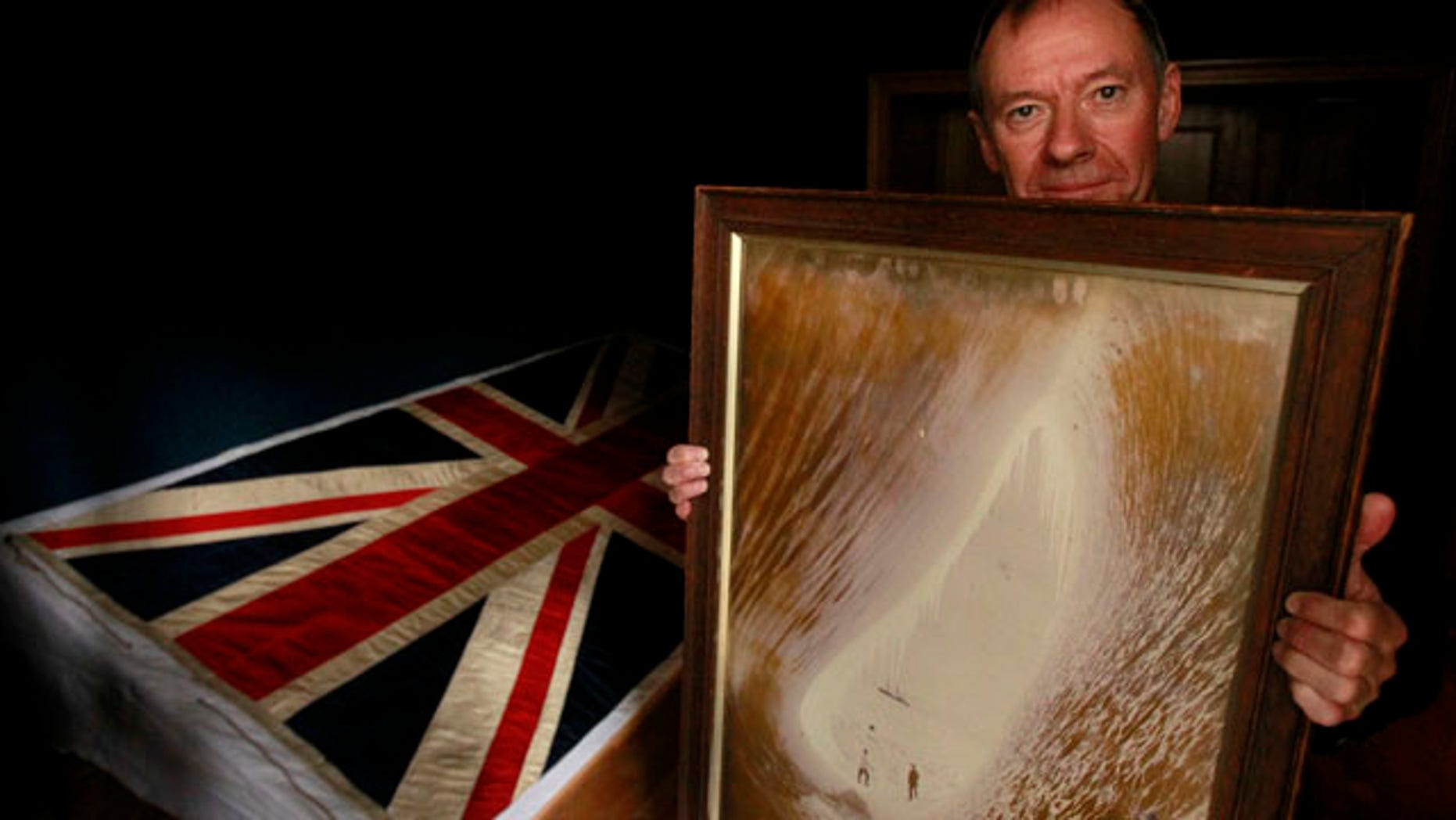 Sept. 20, 2010: Adrian Raeside from Canada, holds a photograph of his grandfather Sir Charles Seymour Wright and great-uncle Thomas Griffith Taylor in front of a silk union flag that belonged to captain Robert Falcon Scott and was used on the two expeditions he led to the Antarctic at the Christie's auction house in London.