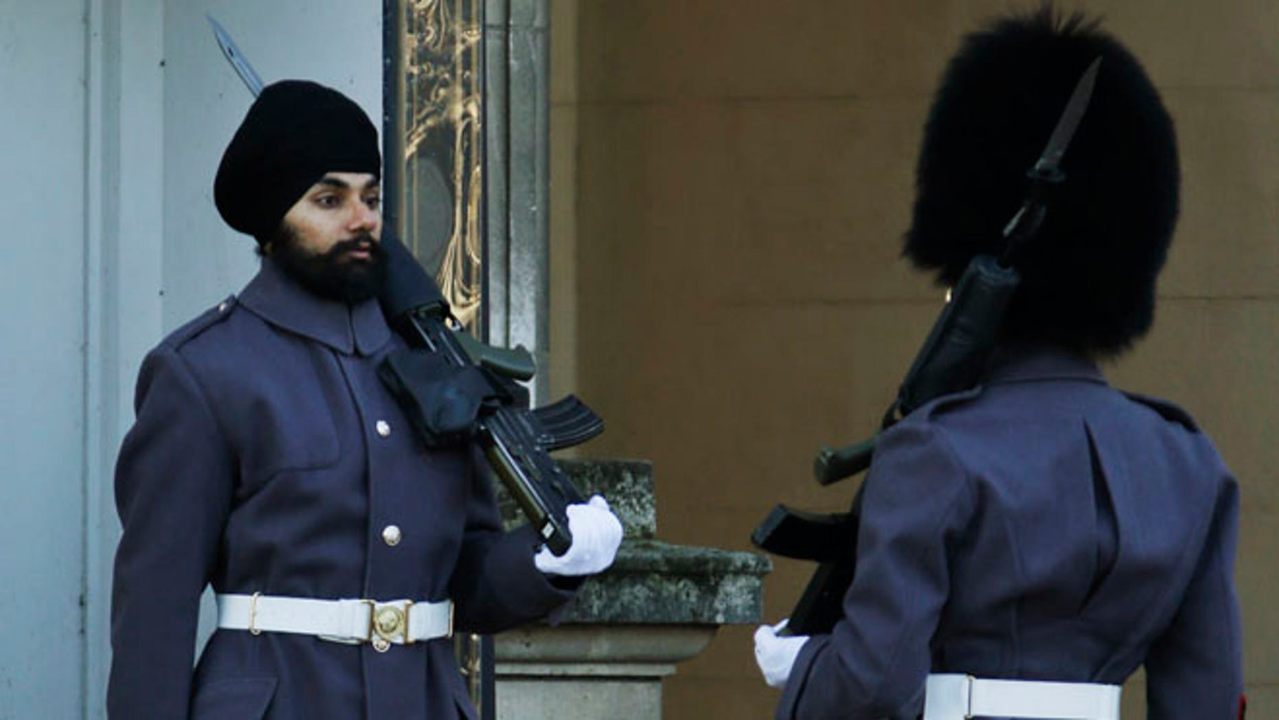 Dec. 11: An officer, right, checks Jatinderpal Singh Bhullar, 25, a Sikh soldier with the Scots Guards, performs guarding duties outside Buckingham Palace in London.