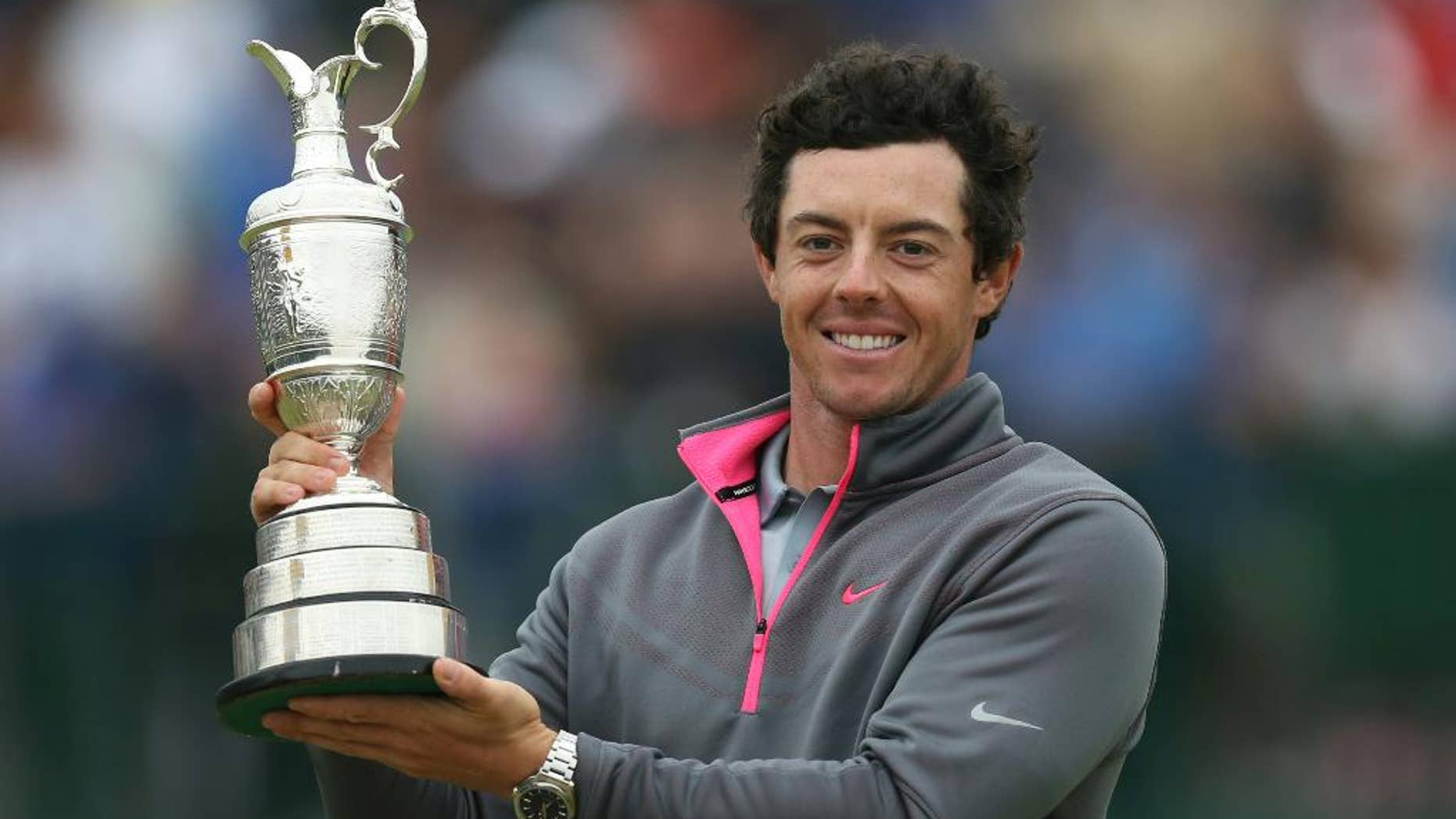 FILE - In this Sunday, July 20, 2014 file photo, Rory McIlroy of Northern Ireland holds up the Claret Jug trophy after winning the British Open Golf championship at the Royal Liverpool golf club, Hoylake, England. McIlroy won't be back to defend his title in the British Open. The world's No. 1 player announced Wednesday, July 8, 2015 that a ruptured ligament in his left ankle will keep him from St. Andrews to play in the British Open. (AP Photo/Scott Heppell, File)