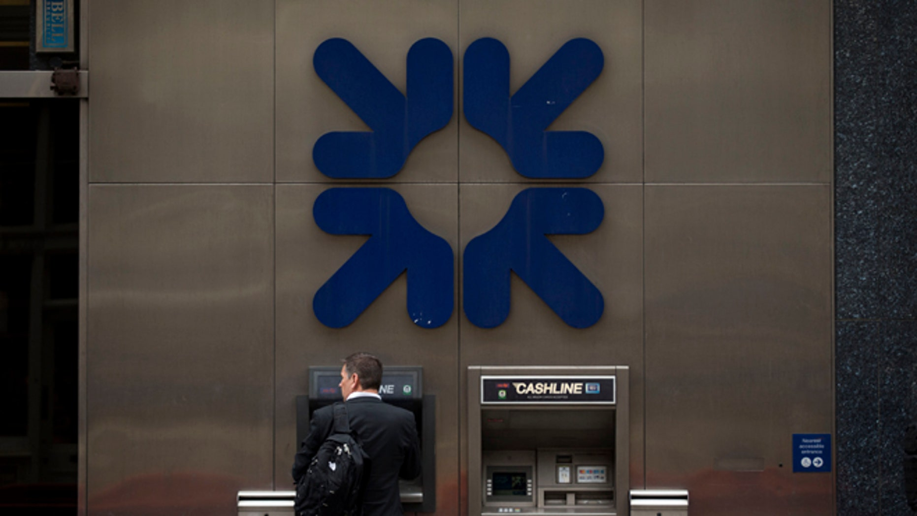 June 13, 2013: A man stands under a RBS, Royal Bank of Scotland, logo as he uses an ATM outside a branch of the bank in London.