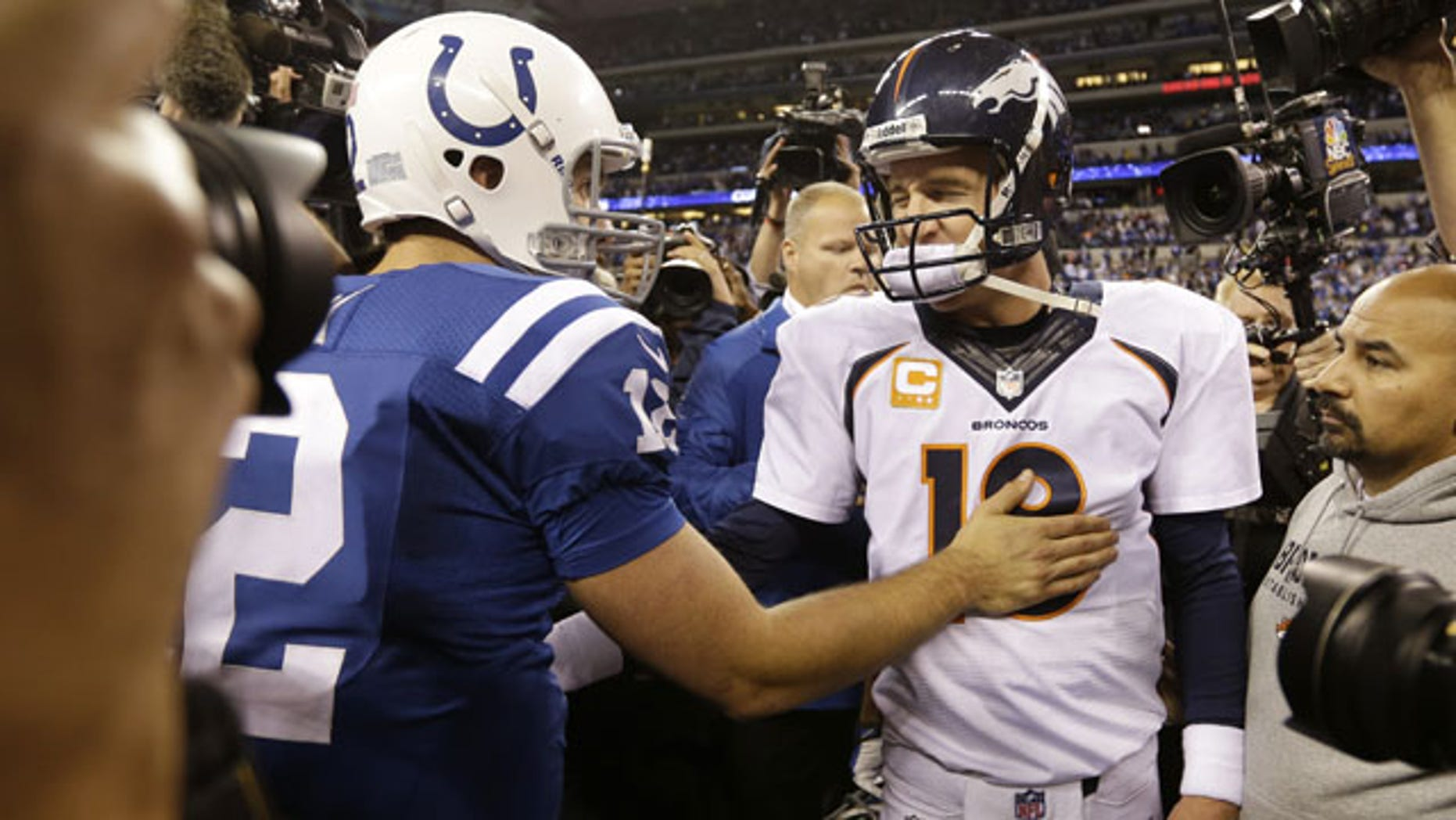 October 20, 2013: Denver Broncos quarterback Peyton Manning, right, greets Indianapolis Colts quarterback Andrew Luck (12) after an NFL football game in Indianapolis. The Colts won 39-33. (AP Photo/Michael Conroy)