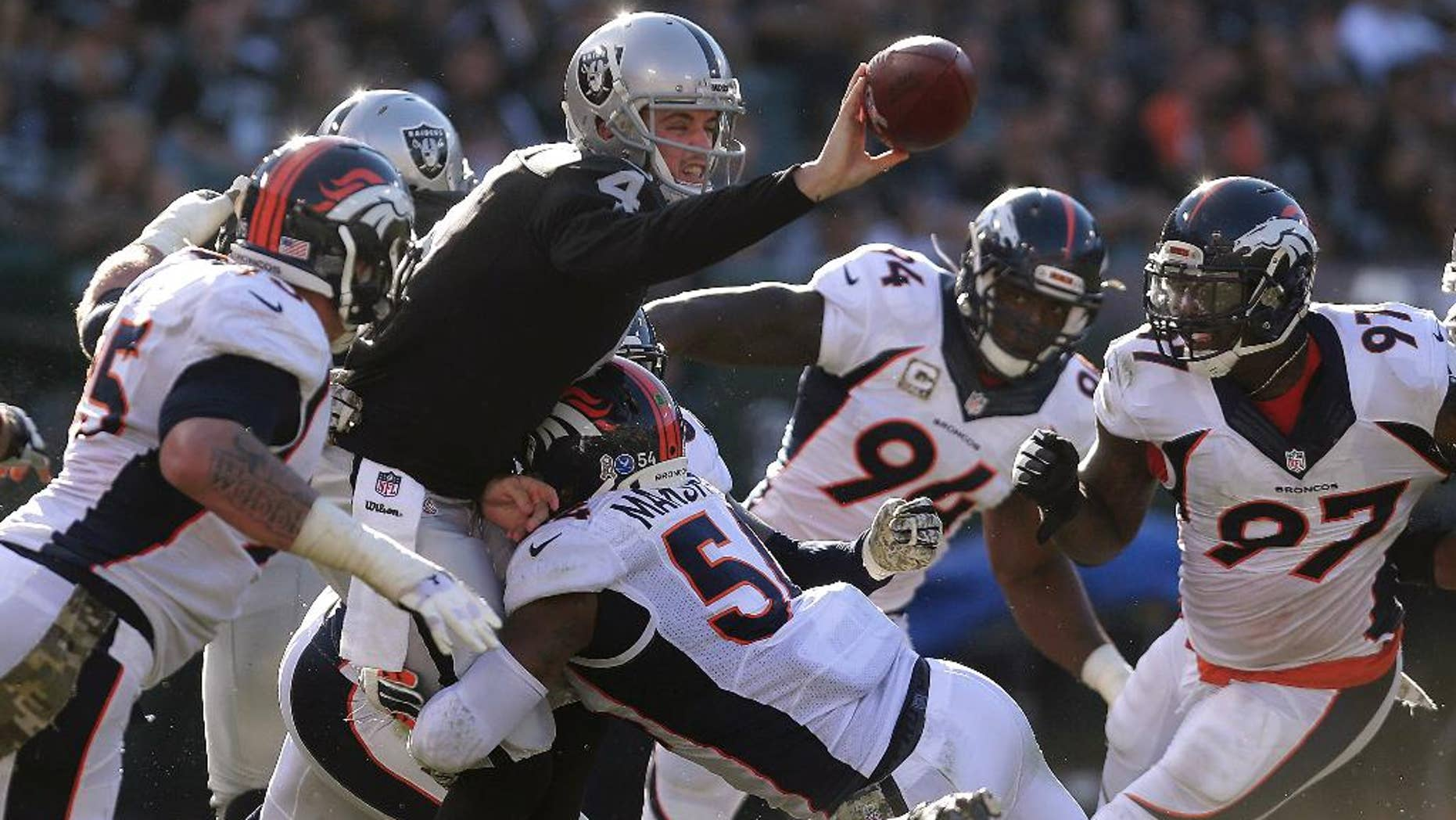 Oakland Raiders quarterback Derek Carr (4) gets rid of the ball as he is pressured by Denver Broncos linebacker Brandon Marshall (54) during the third quarter of an NFL football game in Oakland, Calif., Sunday, Nov. 9, 2014. Carr threw the ball to offensive tackle Khalif Barnes, who fumbled; the ball was recovered by Broncos cornerback Chris Harris. (AP Photo/Marcio Jose Sanchez)