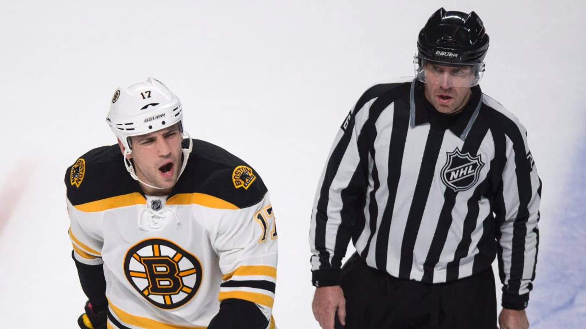 Boston Bruins' Milan Lucic, left, reacts as he is escorted off the ice by linesman Michel Cormier after receiving a penalty near the end of an NHL hockey game against the Montreal Canadiens, Thursday, Oct. 16, 2014, in Montreal. The Canadiens won 6-4. (AP Photo/The Canadian Press, Paul Chiasson)
