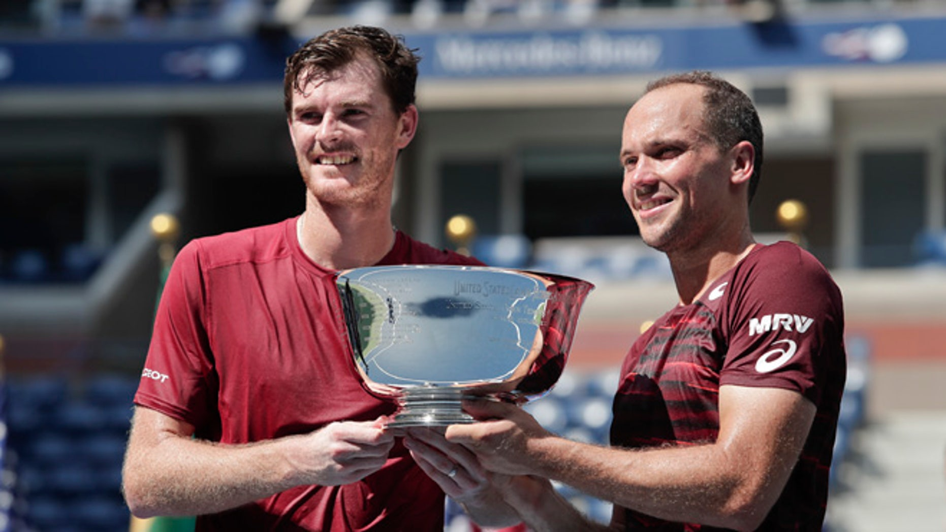 Jamie Murray, of the United Kingdom, left, and Bruno Soares, of Brazil, pose for a photo with the championship trophy after beating Pablo Carreno Busta, of Spain, and Guillermo Garcia-Lopez, of Spain, to win the men's doubles final of the U.S. Open tennis tournament, Saturday, Sept. 10, 2016, in New York. (AP Photo/Julie Jacobson)