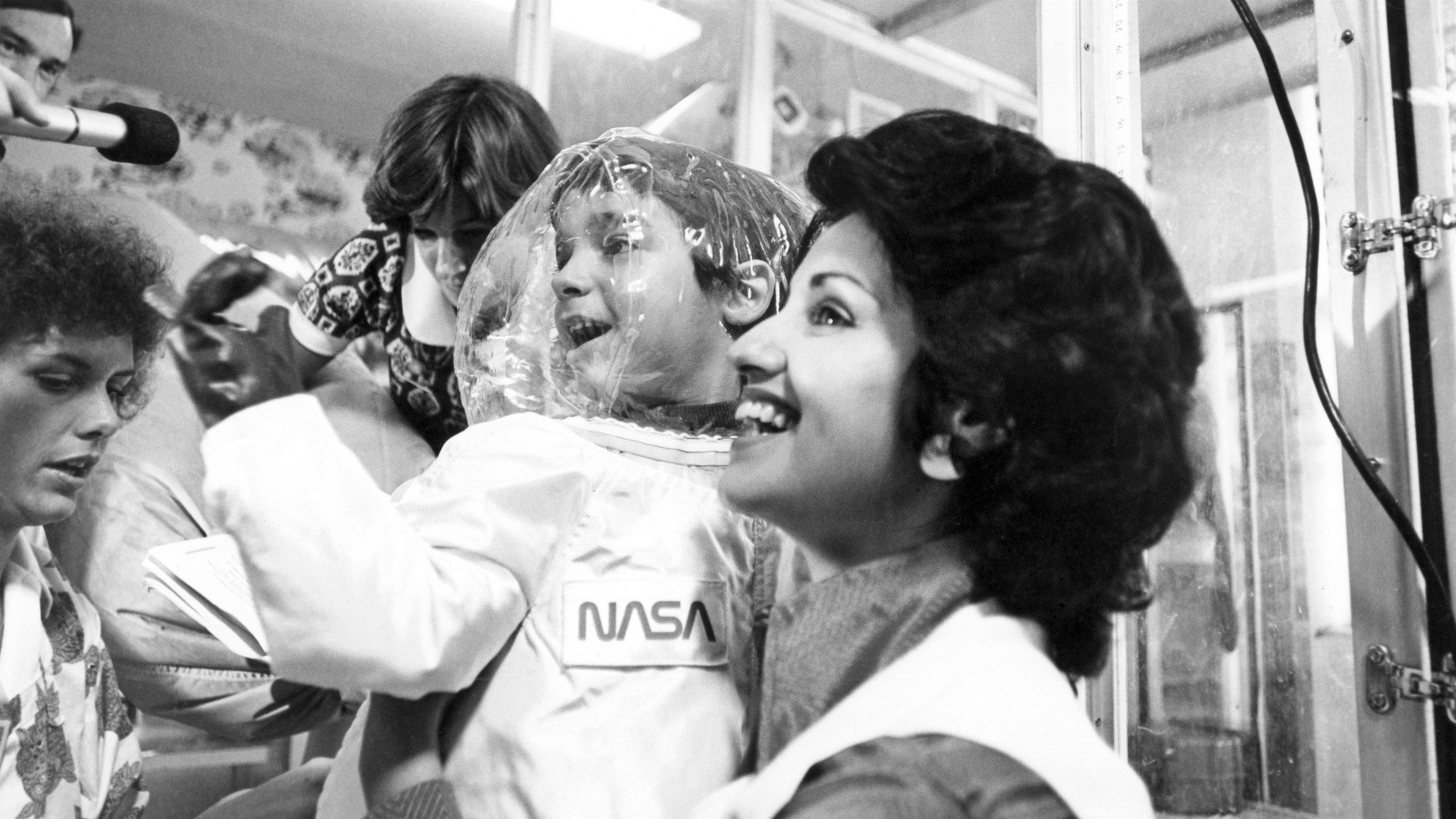 Carol Ann holds her son David while he wears a suit specially designed by NASA, on July 29, 1977.
