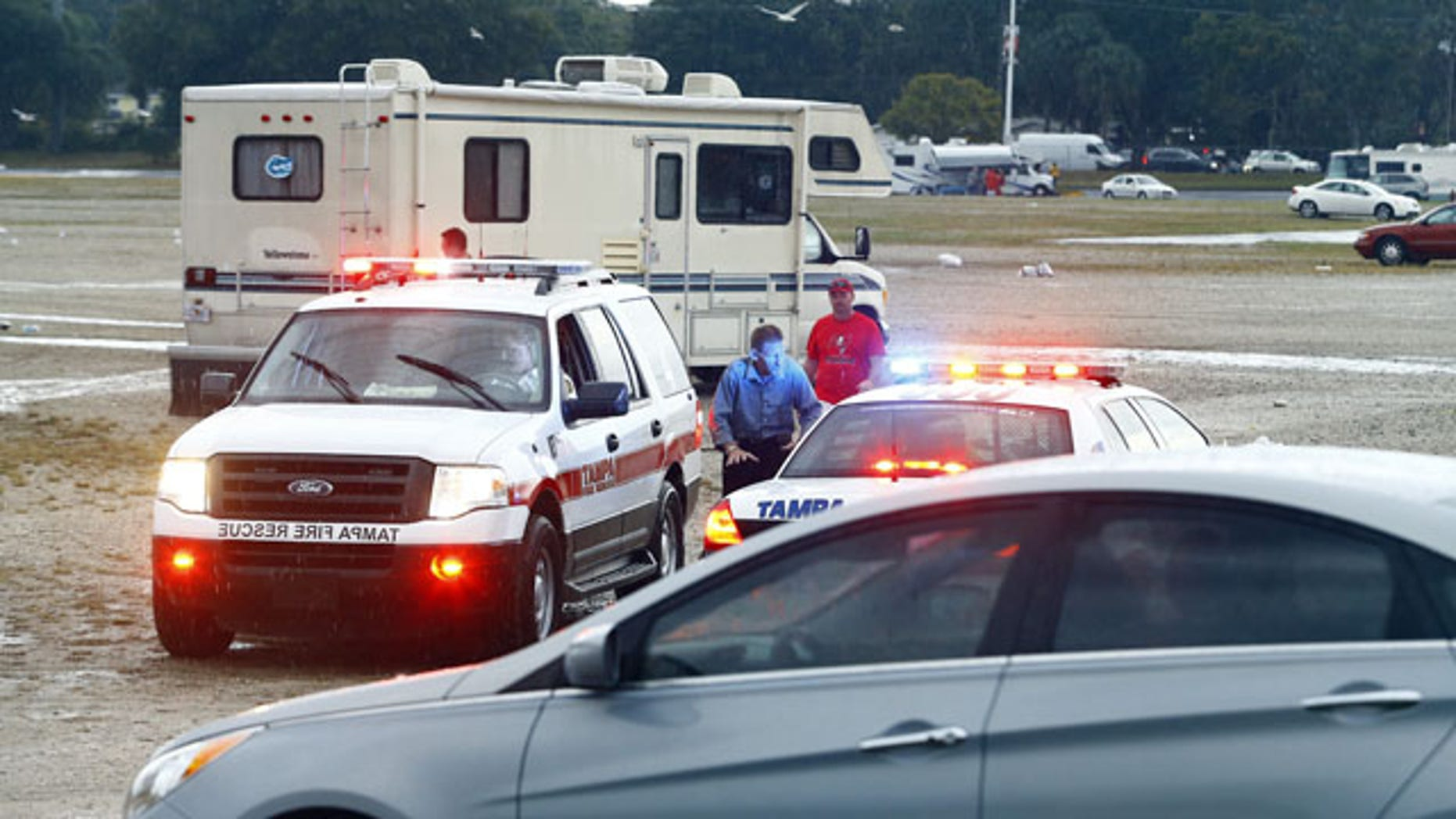 Dec. 21, 2014: Tampa Police Officers talk to spectators after football fans were reportedly taken to the hospital with injuries after a lightning strike near Raymond James Stadium. (AP Photo/Brian Blanco)