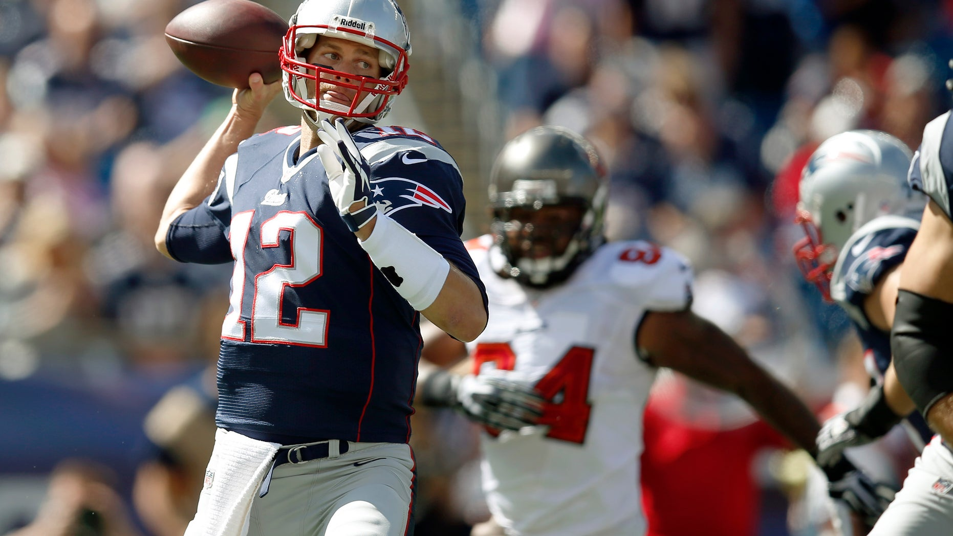 New England Patriots quarterback Tom Brady (12) passes while pursued by Tampa Bay Buccaneers defensive end Adrian Clayborn (94) in the first half of an NFL football game Sunday, Sept. 22, 2013, in Foxborough, Mass. (AP Photo/Elise Amendola)