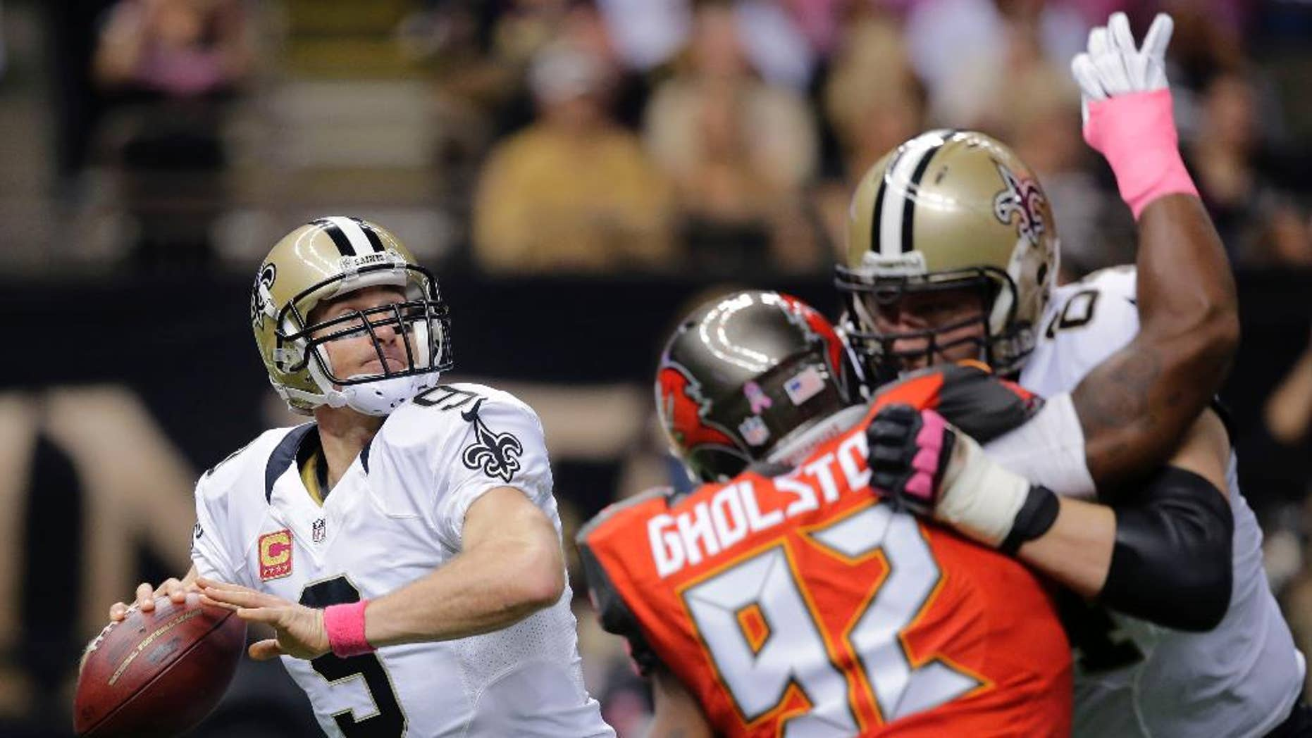 New Orleans Saints quarterback Drew Brees (9) drops back to pass under pressure from Tampa Bay Buccaneers defensive end William Gholston (92) in the first half of an NFL football game in New Orleans, Sunday, Oct. 5, 2014. (AP Photo/Bill Haber)
