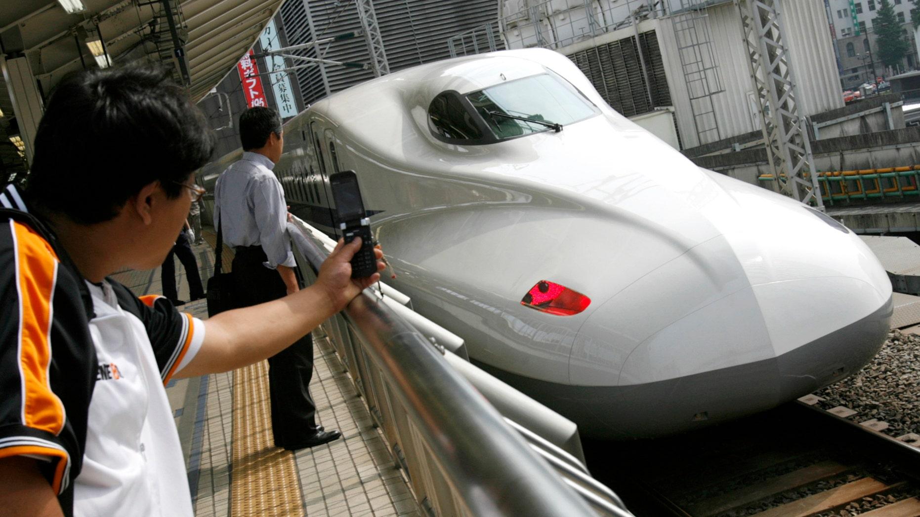 File photo - Men look at Japan Railway's N700 bullet train standing at a platform of Tokyo Station in Tokyo July 6, 2007.