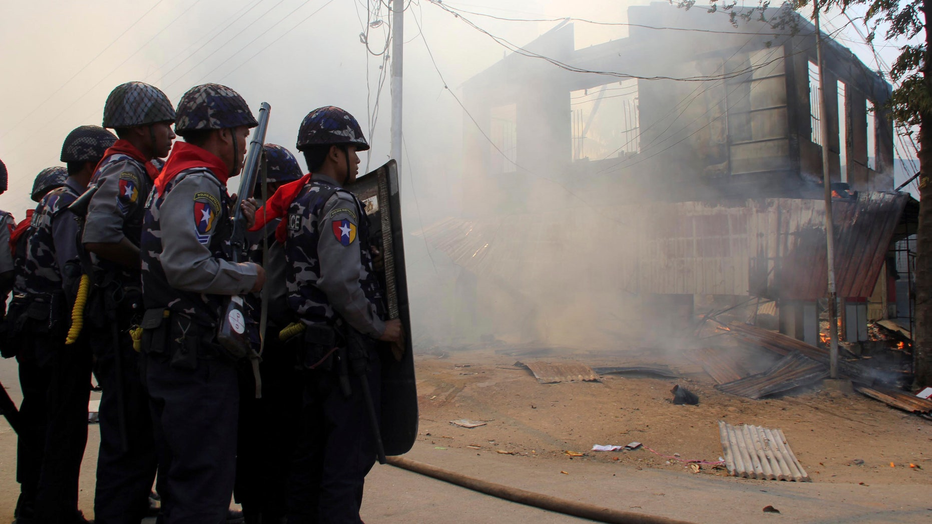 March. 21, 2013: This photo shows armed Burma police officers provide security around a smoldering building following ethnic unrest between Buddhists and Muslims in Meikhtila, Mandalay division, about 340 miles north of Yangon, Burma.