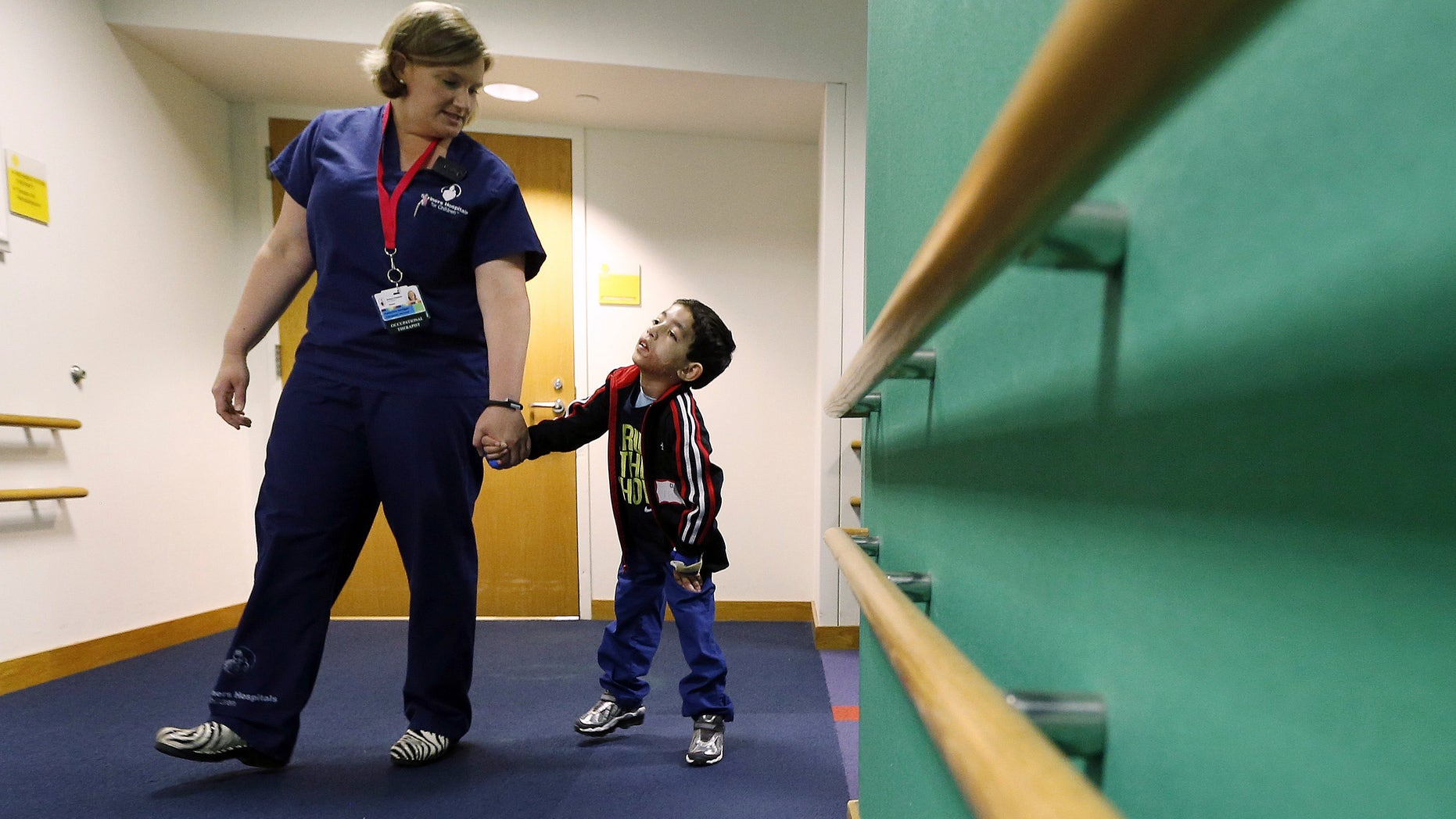 Therapist Katherine Hartigan walks with Ihor Lakatosh at Shriners Hospital for Children in Boston. (AP Photo/Michael Dwyer)