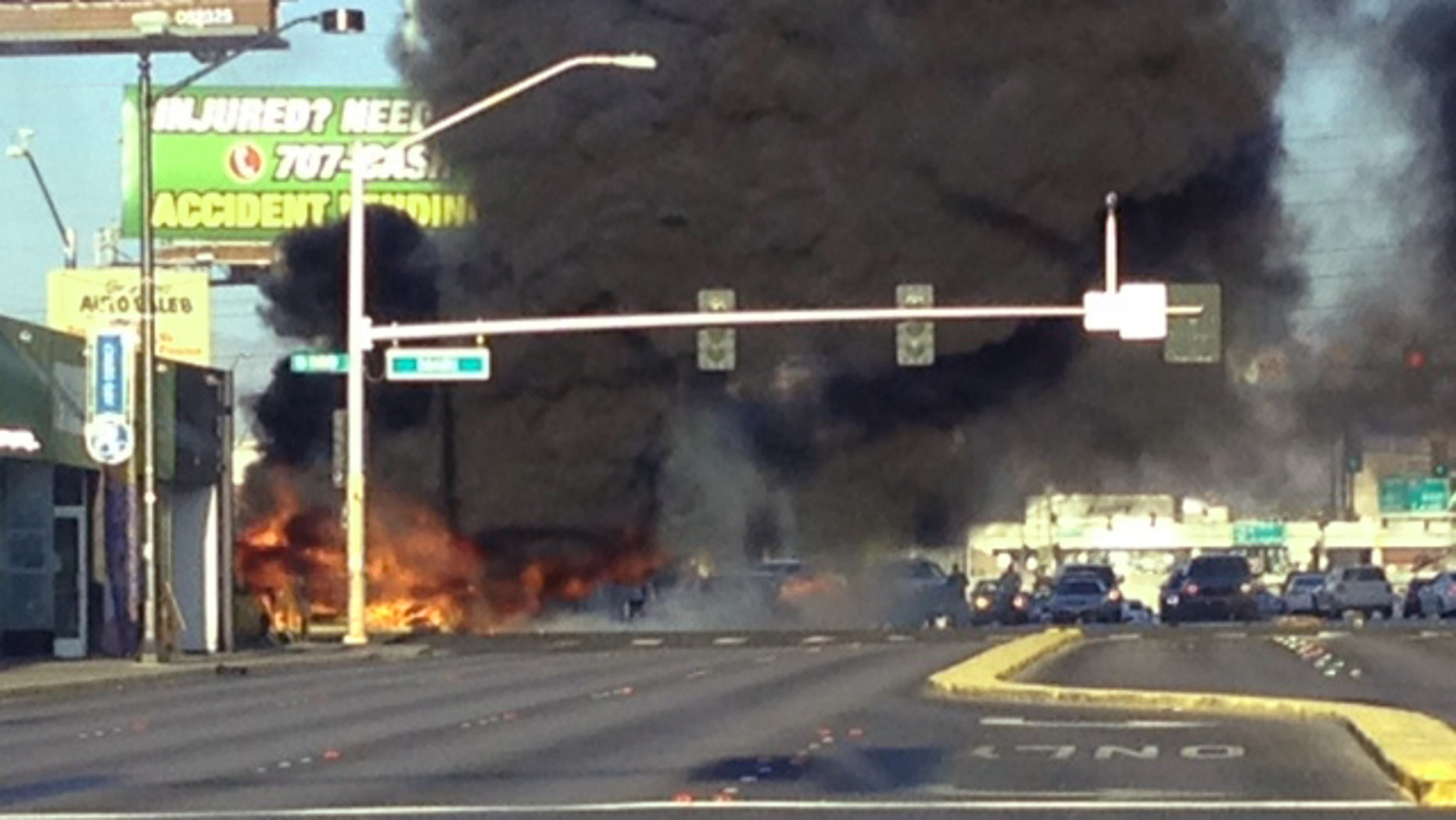Smoke filled the sky after a fire tore through a mini bus following a collision in Las Vegas, on Saturday, Sept. 5, 2015. Fire officials say a burning mini bus was found lying on its side on the sidewalk and a car was in the middle of the intersection.  According to investigators, two people were unable to flee the bus and died at the scene. Four other passengers were taken to the hospital for burns. There were no other injuries.